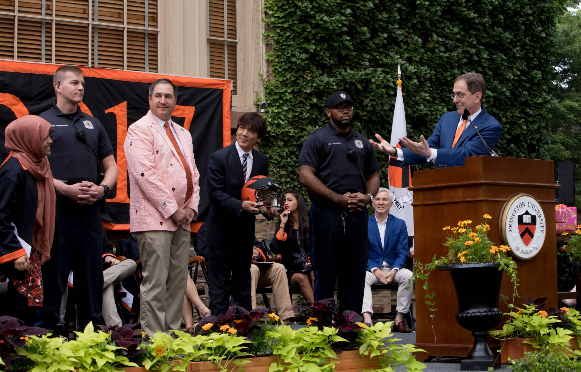 President Eisgruber presenting football helmut to students at Class Day 2017 ceremony
