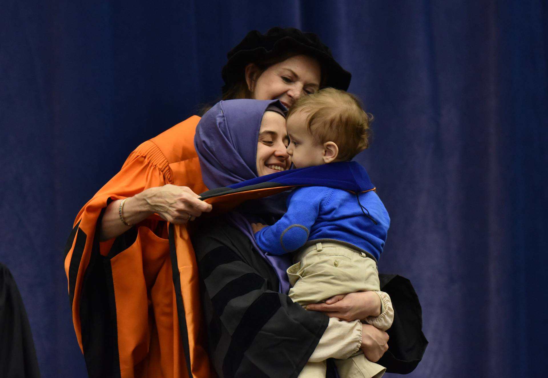 Student is hooded with child in arms