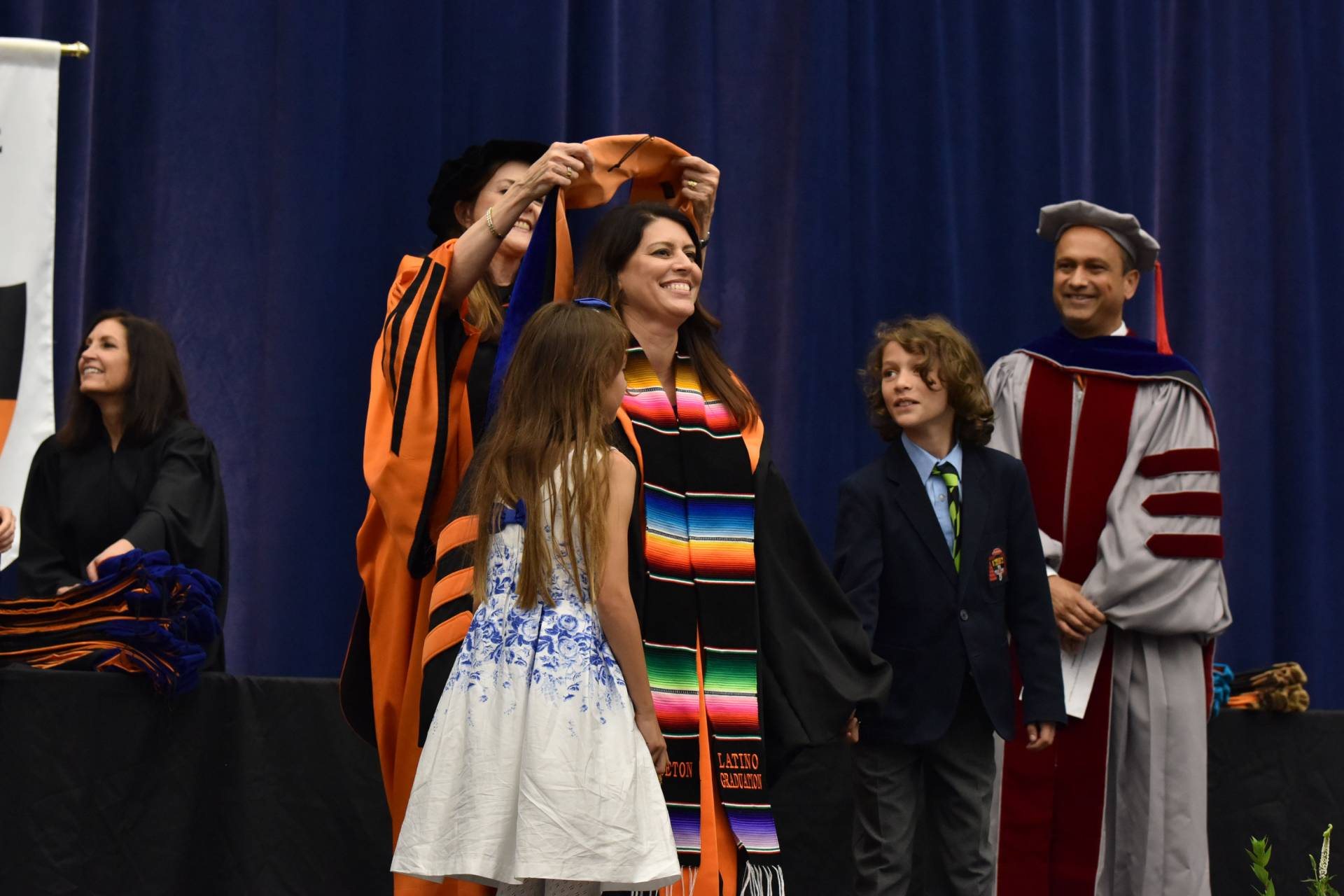 Student stands with son and daughter during hooding