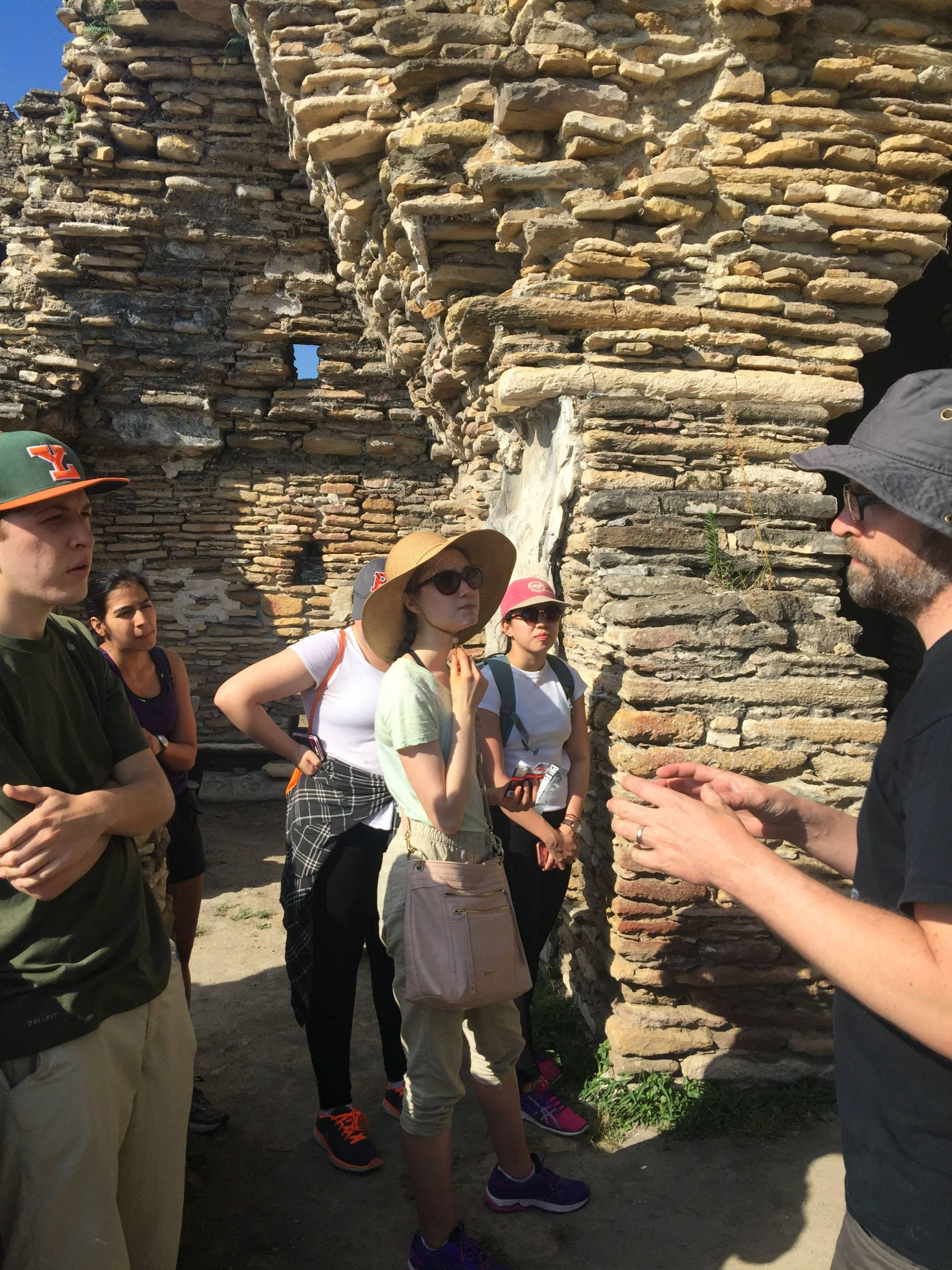 Students and professor amid palatial architecture of Tonina