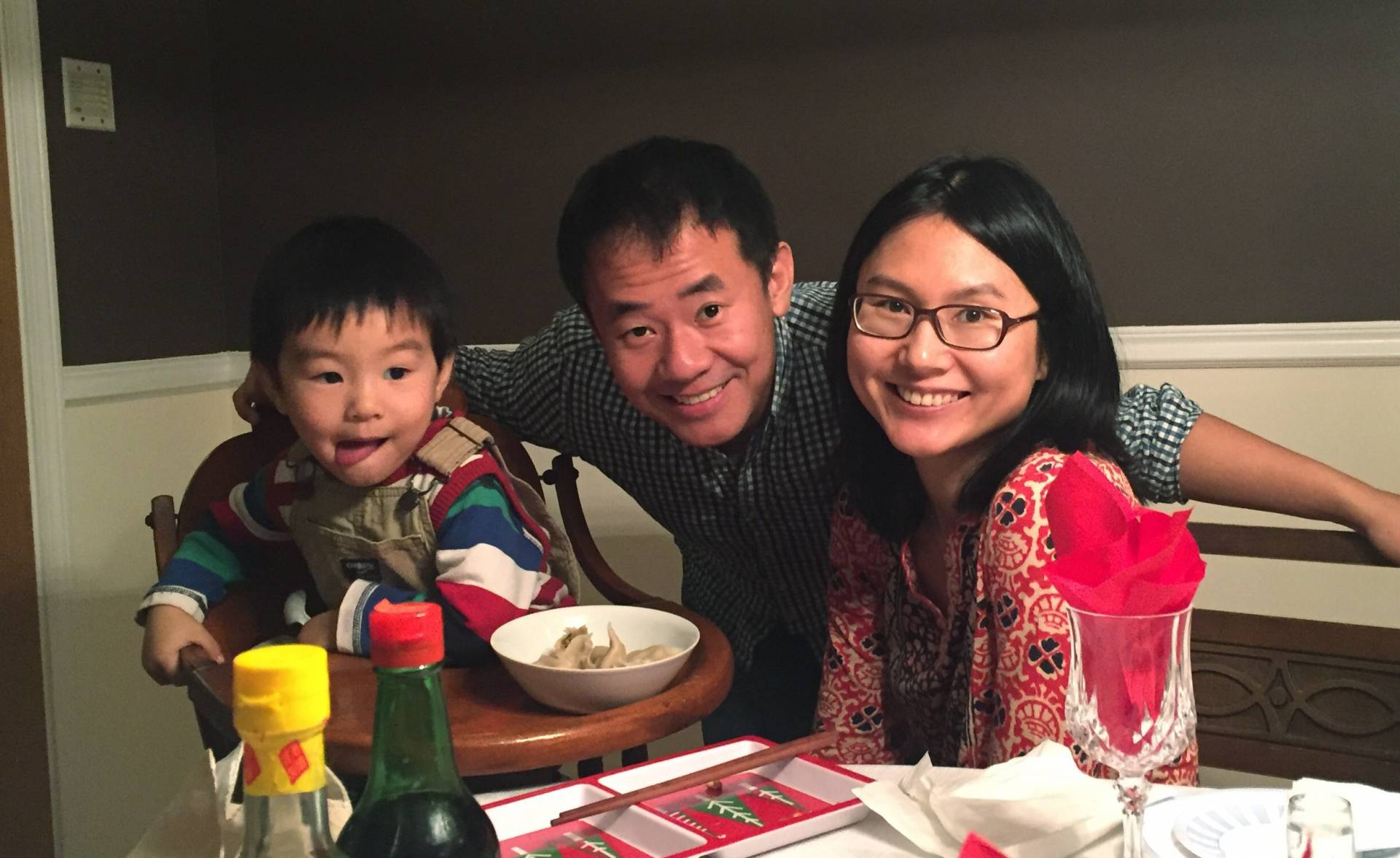 Xiyue Wang, Hua Qu and their son seated at a table