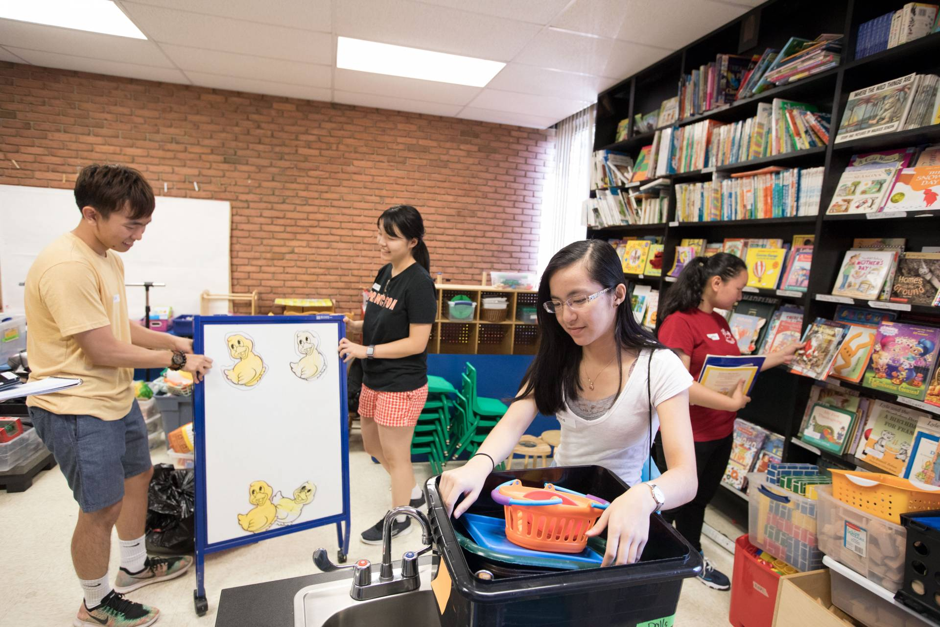Students cleaning YWCA storeroom of books and toys