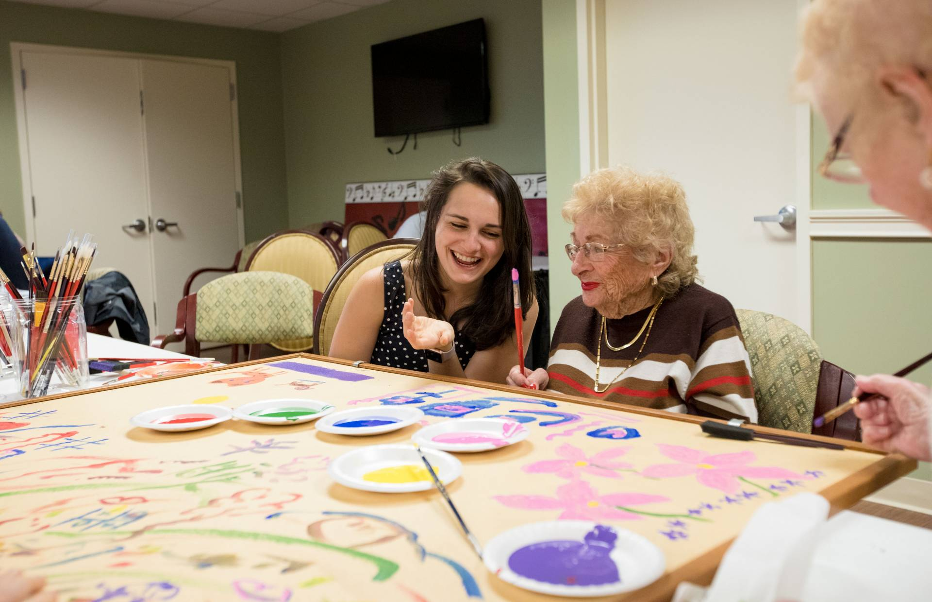 Student helping Brandywine Living resident paint