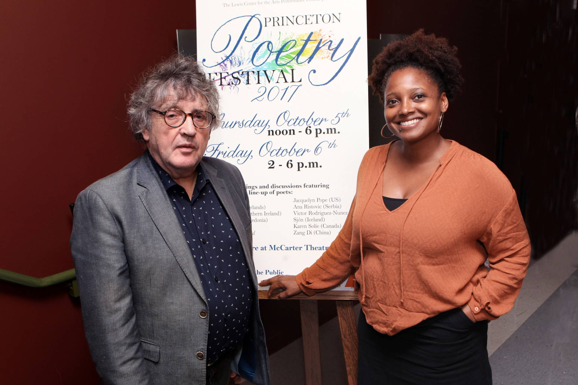 Paul Muldoon and Tracy Smith stand by Poetry Festival poster