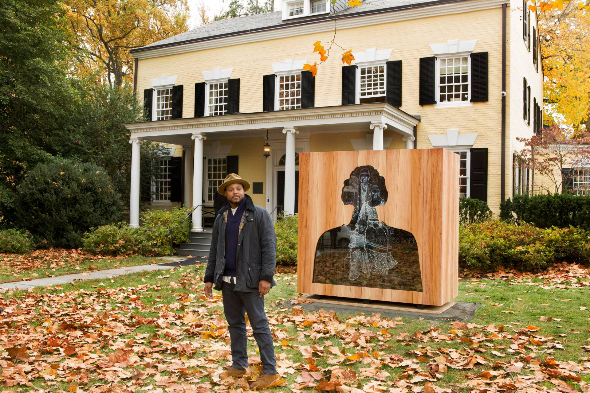 Titus Kaphar standing outside Maclean House in front of his sculpture