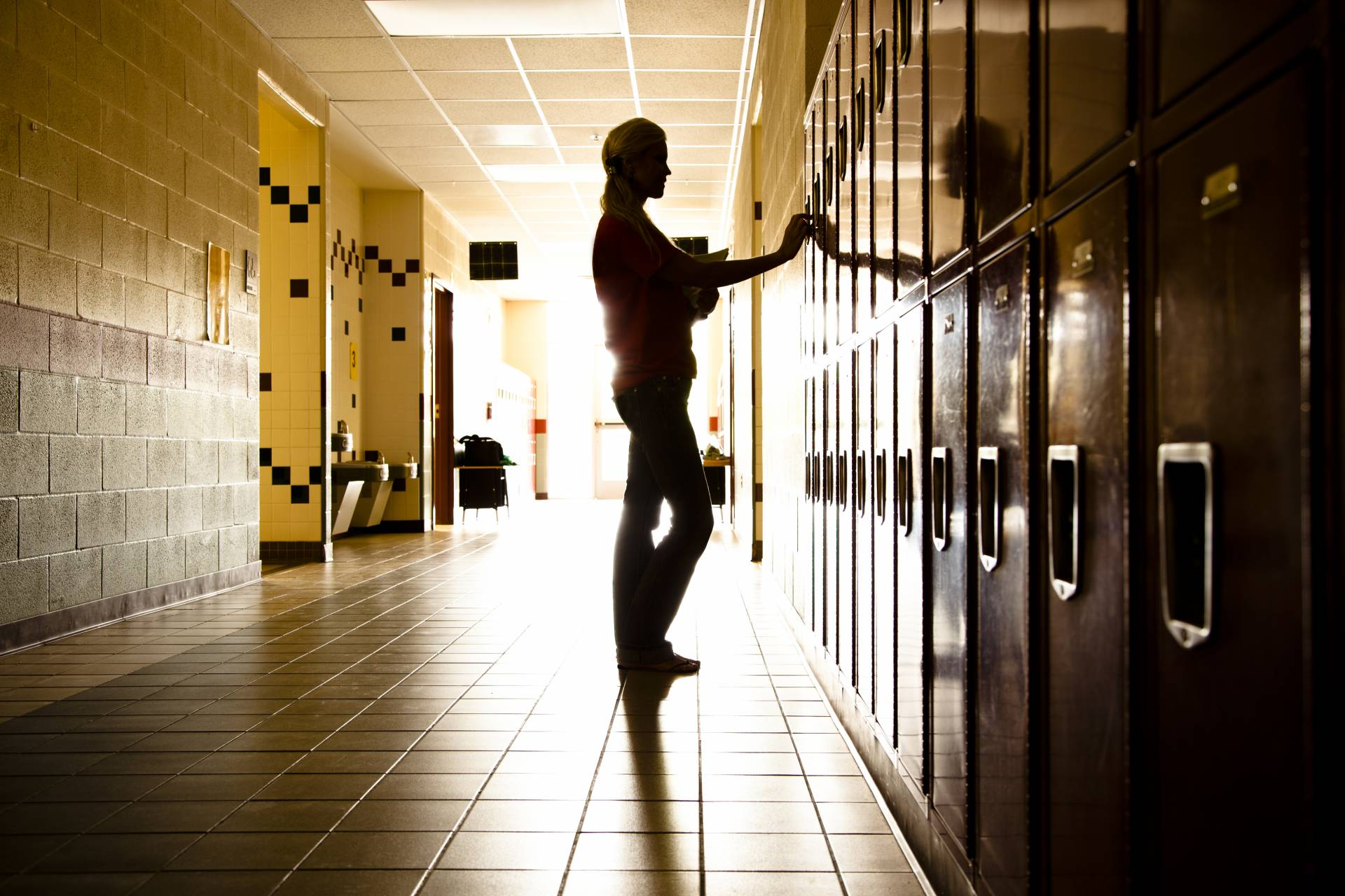 Silhouetted high school student stands at lockers