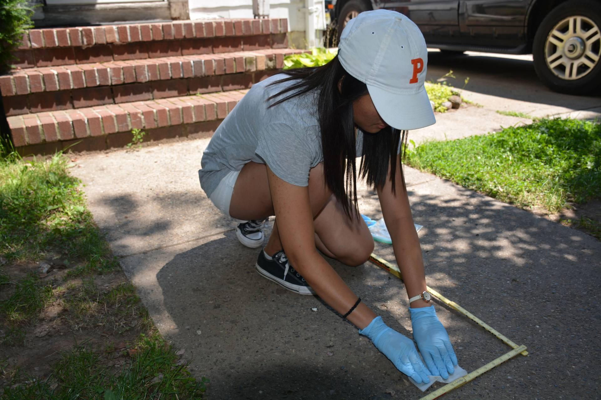 Student taking sample on sidewalk