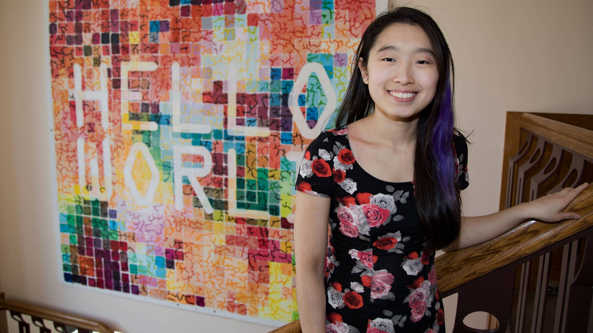 Katherine Lim standing in stairwell in front of Hello World mural