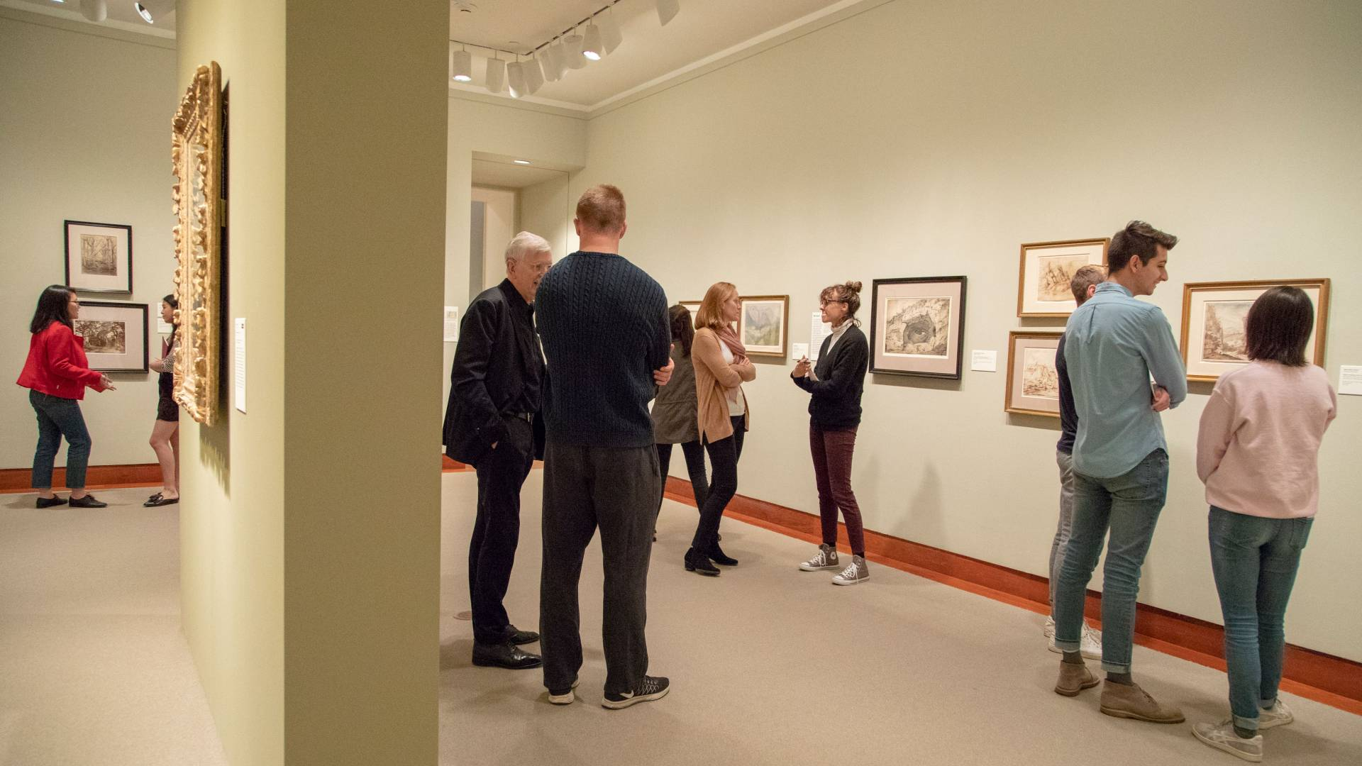 Students and professor looking at Landscapes Behind Cezanne exhibit