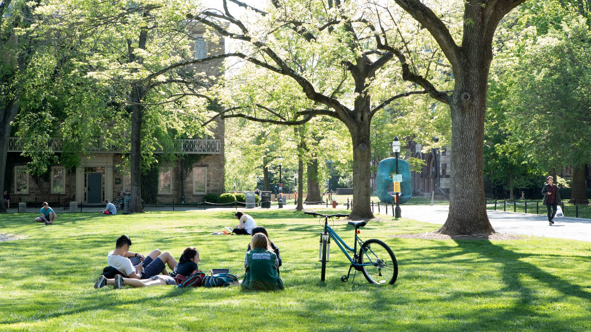Students sitting on lawn on campus by Morrison Hall and Oval With Points sculpture