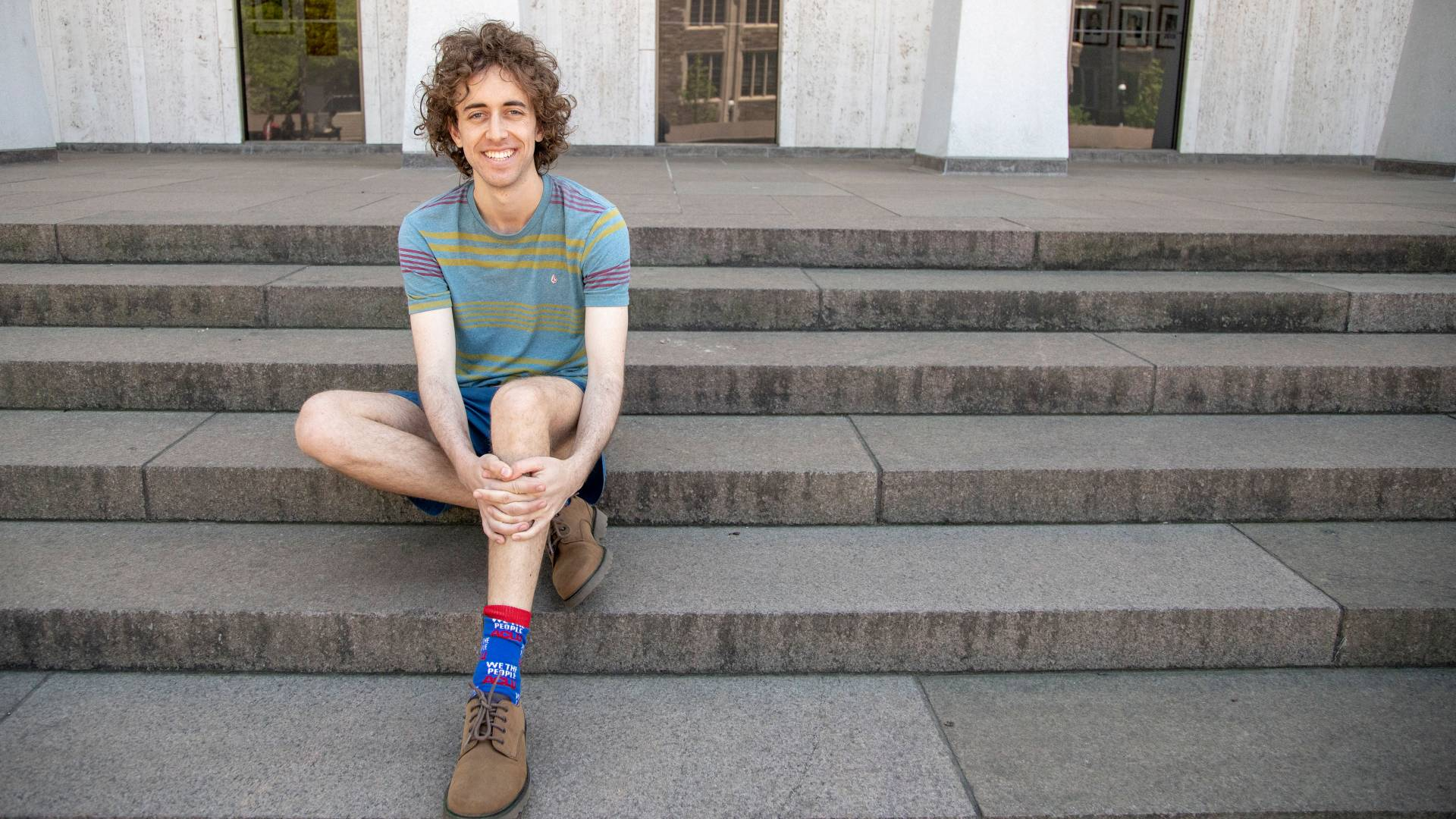 Kyle Berlin sitting on steps outside Woodrow Wilson building