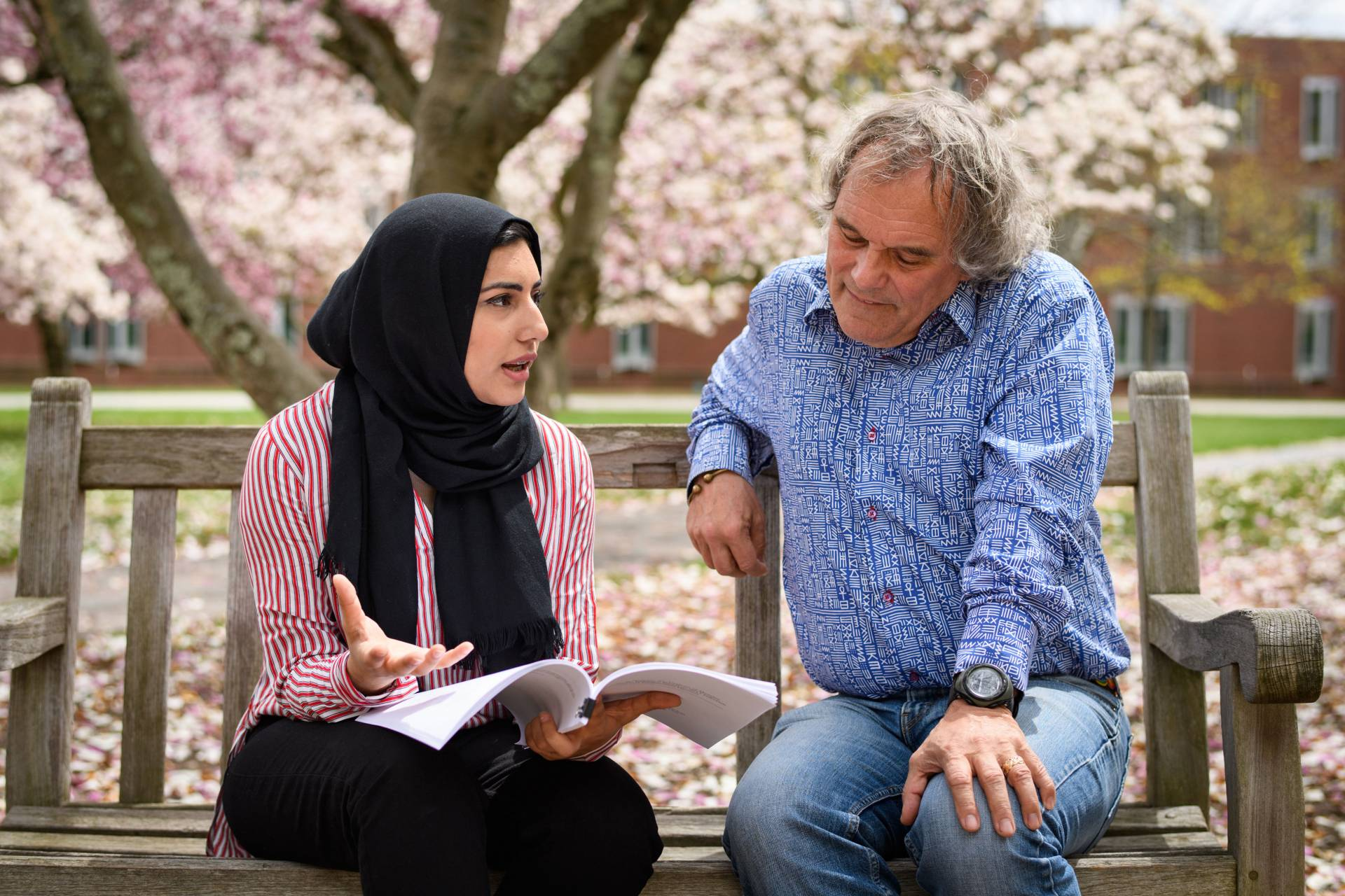 Raia Khan and professor Andrew Dobson sitting outside on bench