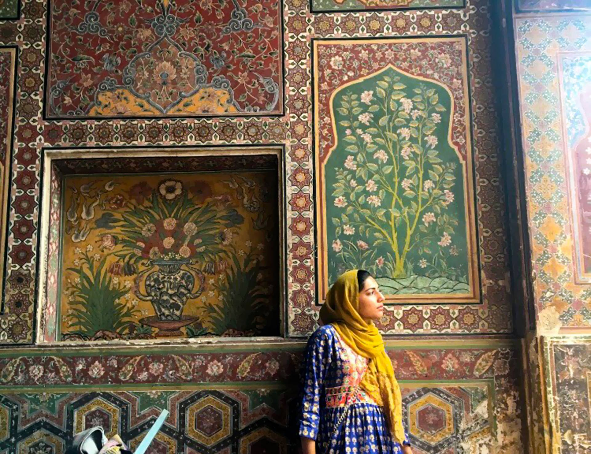 Rabia Khan standing in front of tiled mosque wall