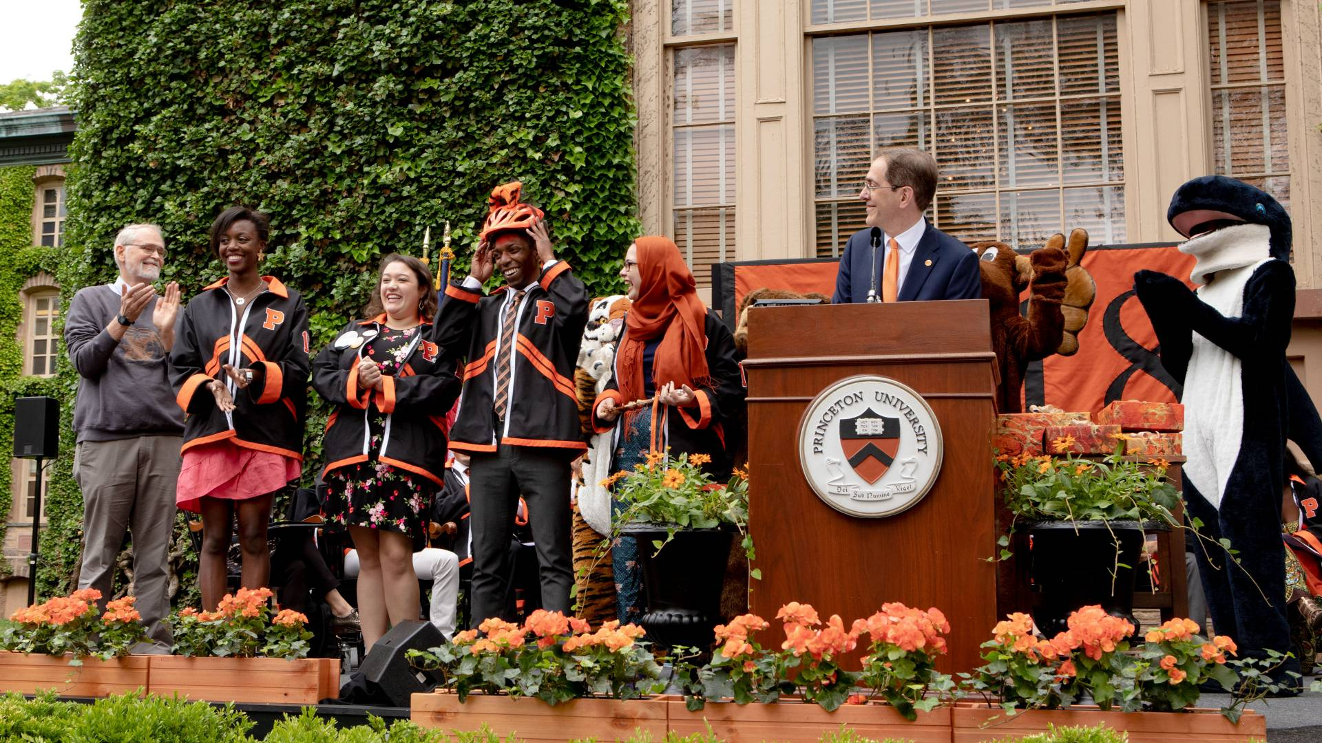 President Eisgruber on stage with students, mascots and professor Kernighan during Class Day ceremony