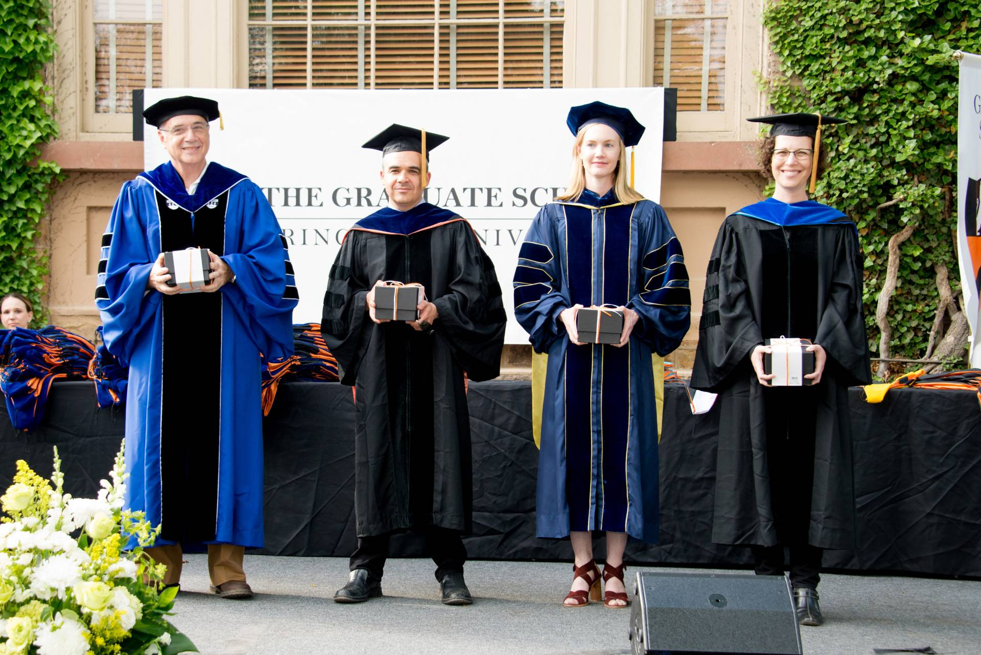 Graduate Mentoring Awards recipients at Hooding Ceremony stand together on stage