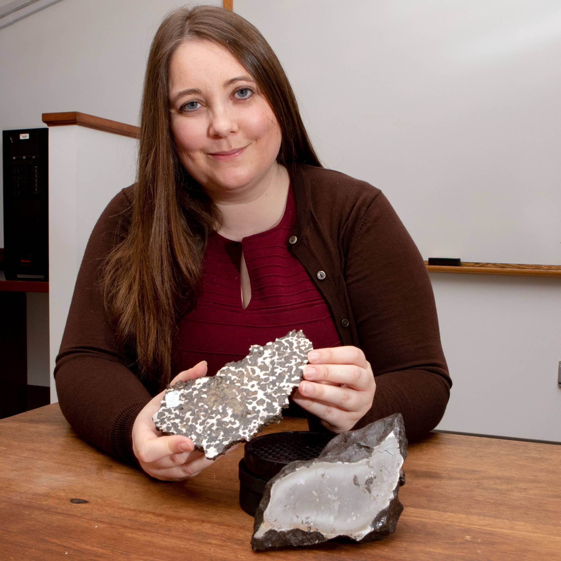 Jessica Irving sits with two meteorites