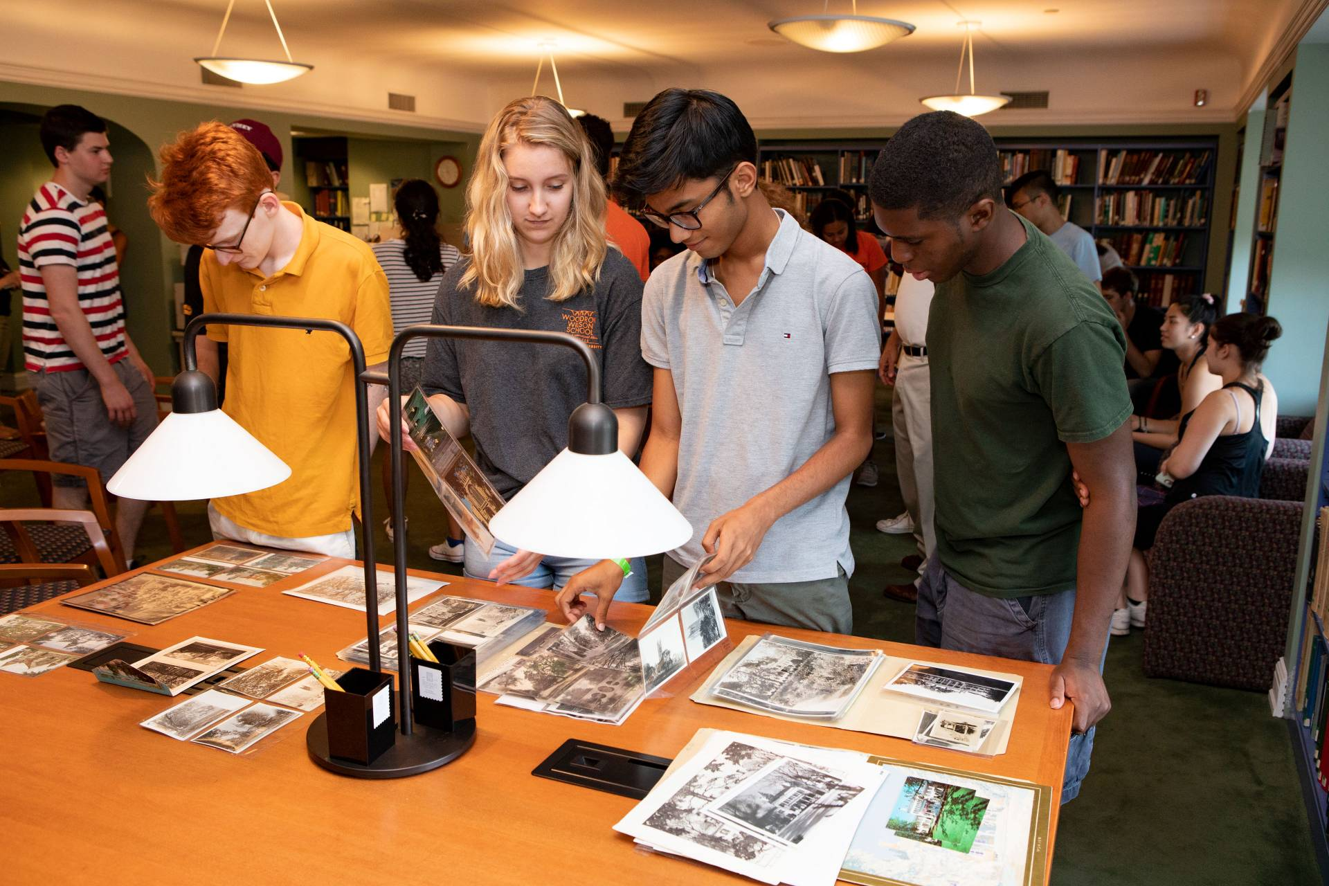 Students looking at old papers, pamphlets and photos of Princeton
