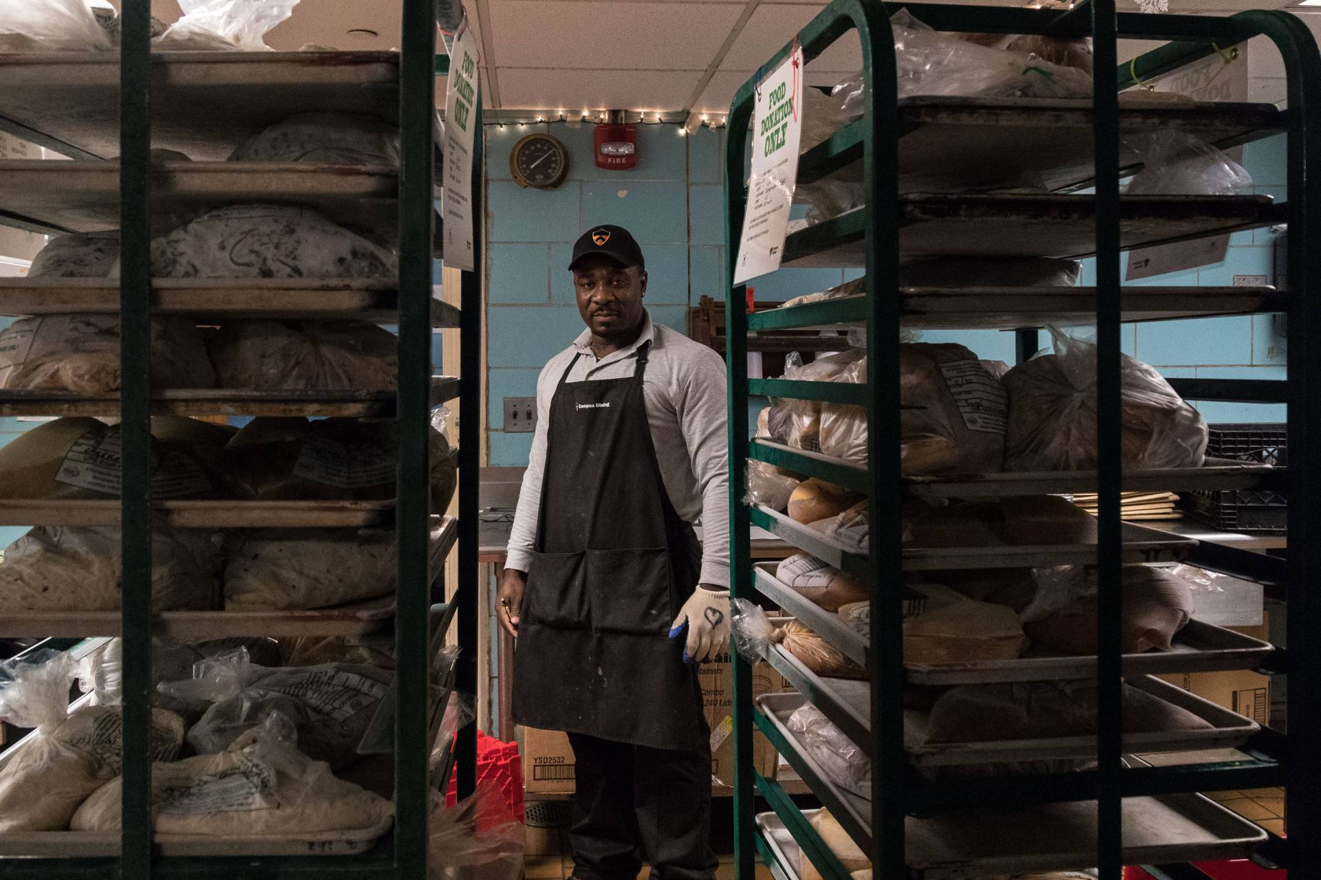 Food service storekeeper Odman Jean Denis standing in between two racks of bread