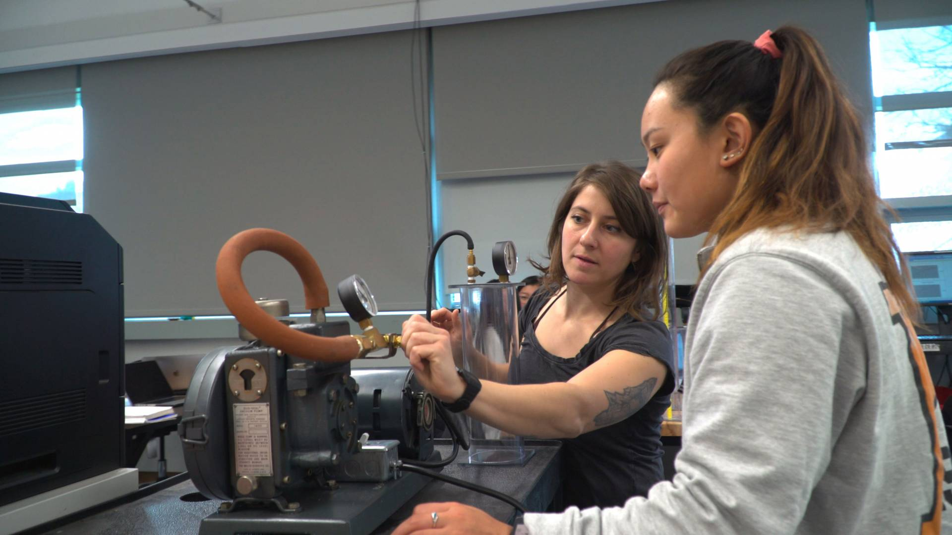 Instructor working with student in physics lab