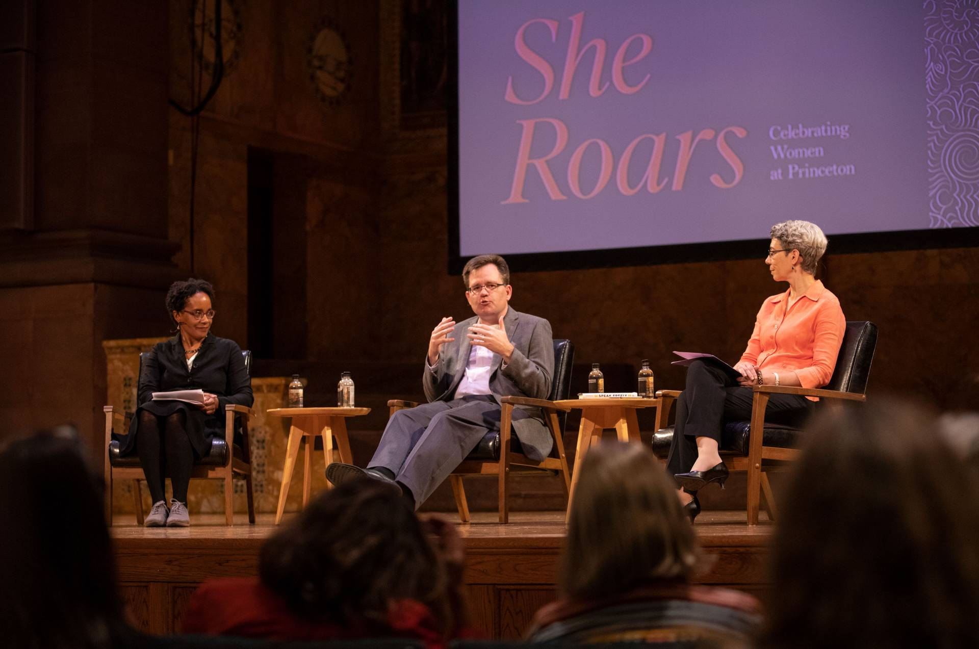 "Carolyn Rouse, Keith Whittington and Michele Minter on stage with ""She Roars"" project on screen"