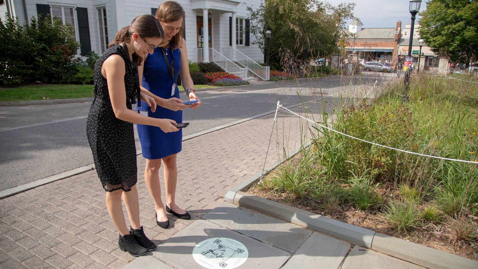 Abby Klionsky '14 showing Caroline Stone '14 how to scan the QR code at the Betsey Stockton Garden outside Firestone Library