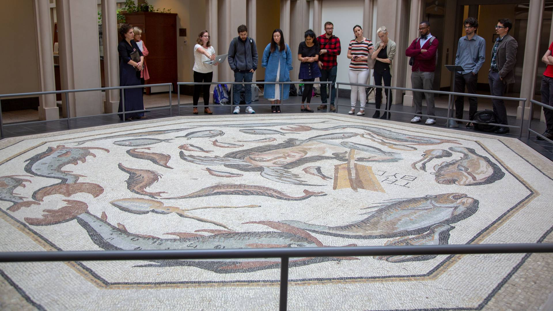 Students looking at large mosaic at Harvard museum