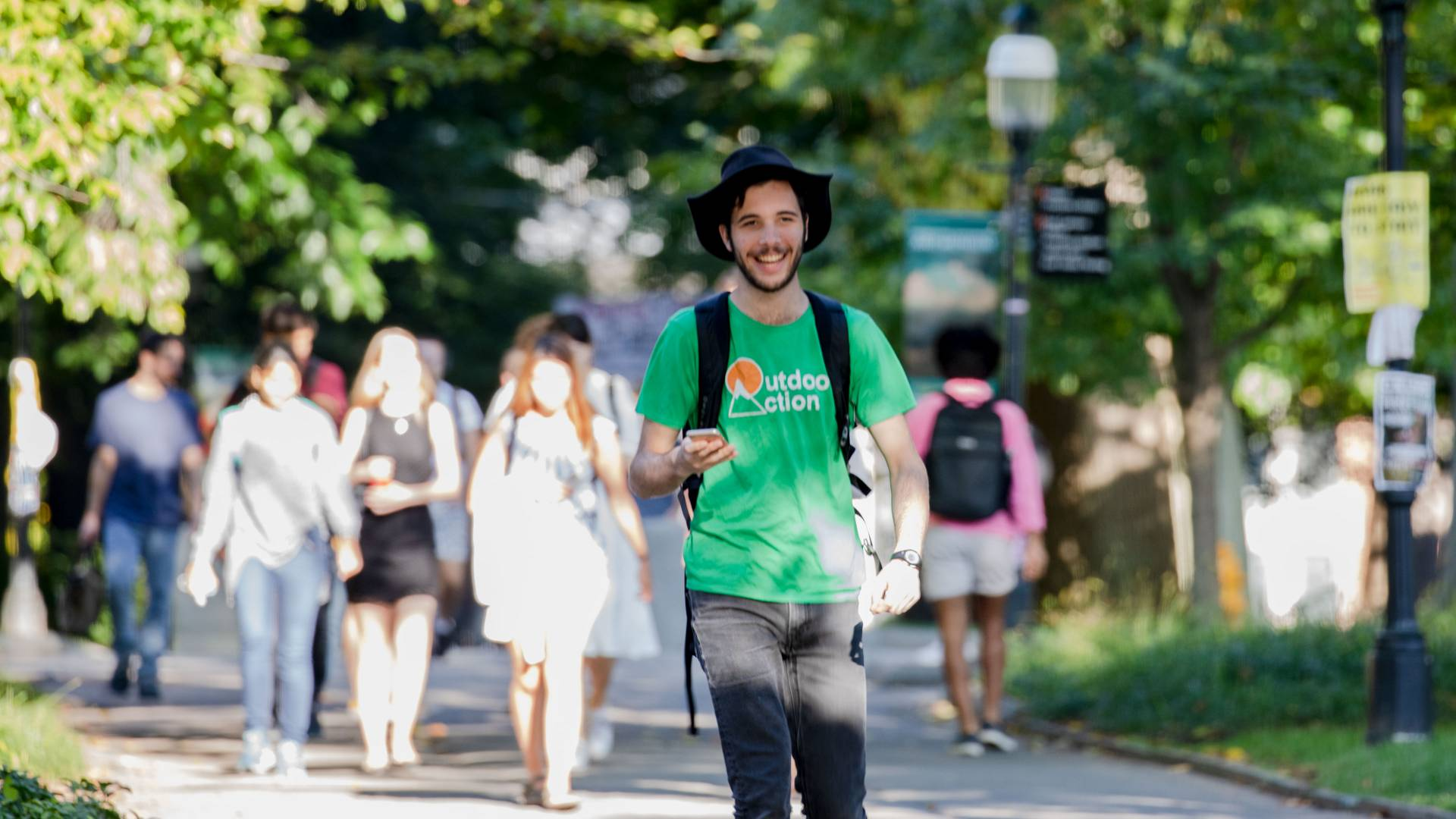 Student with Outdoor Action shirt walking on campus