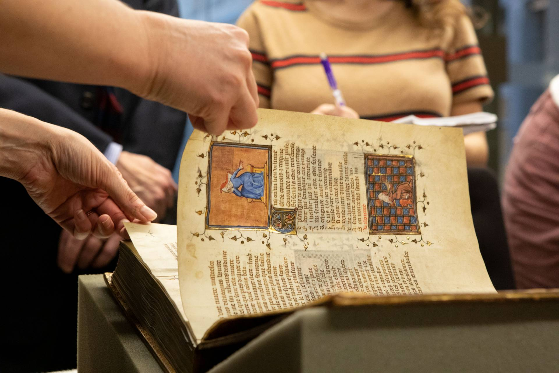 Hand turning page of ancient illuminated manuscript
