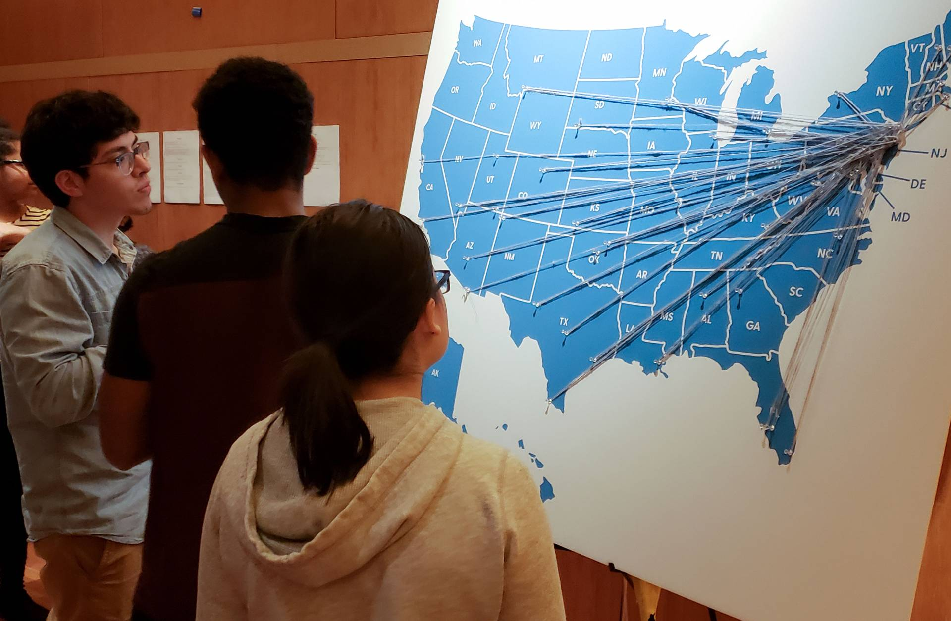 Students looking at map of US with strings and pins marking Breakout Princeton trip locations