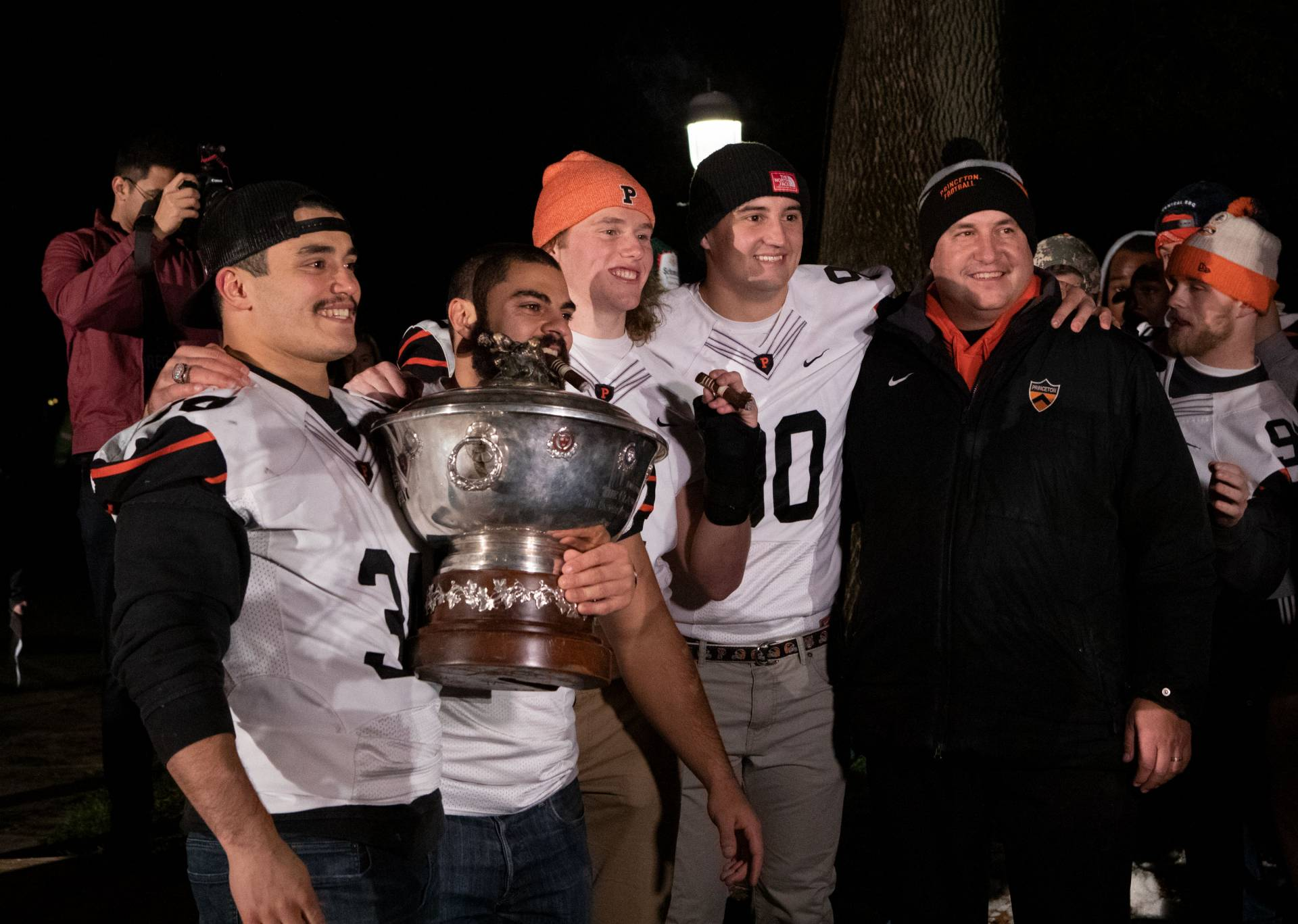 Football team and coach hold the Ivy League championship trophy