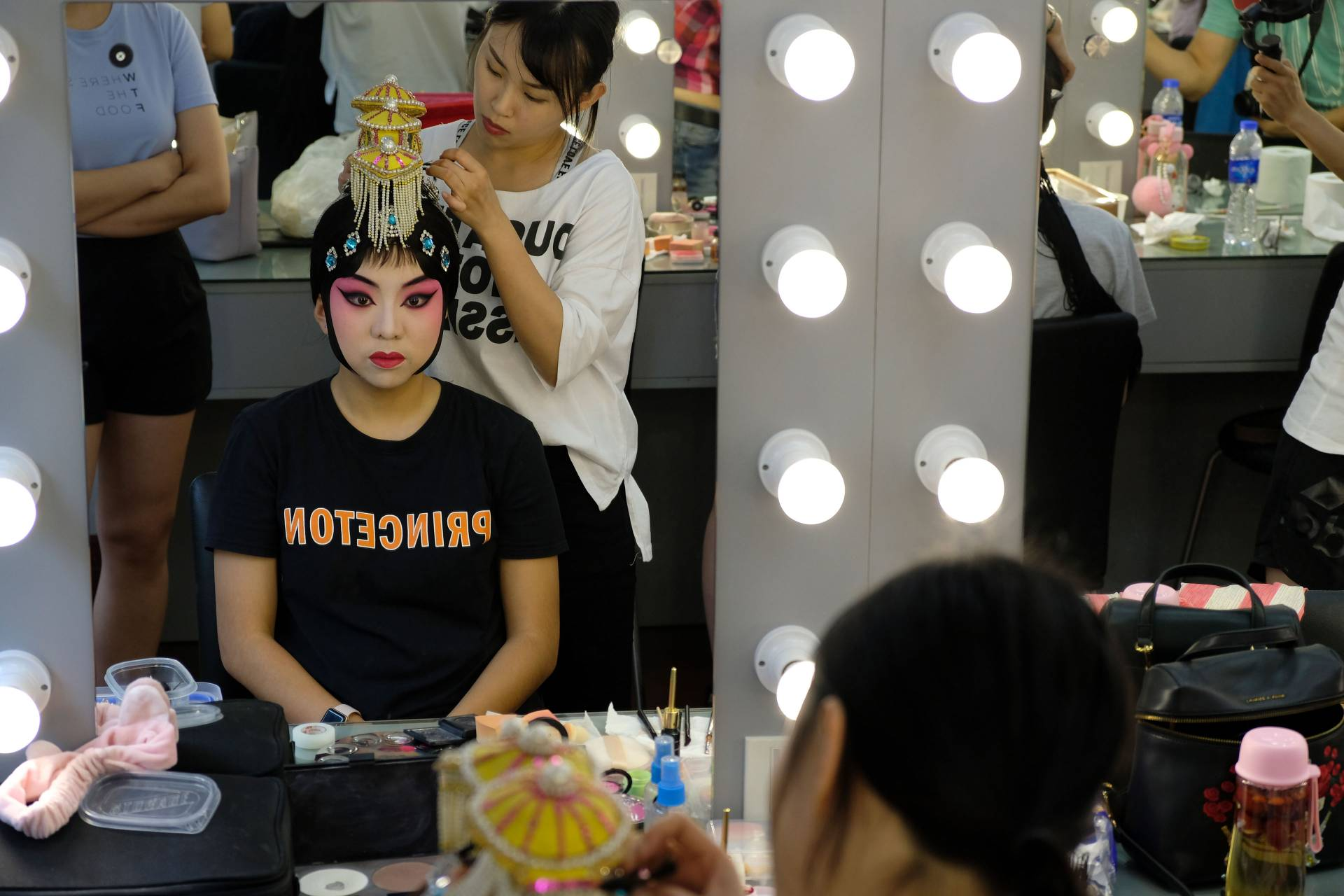Reflection in mirror of student having makeup applied