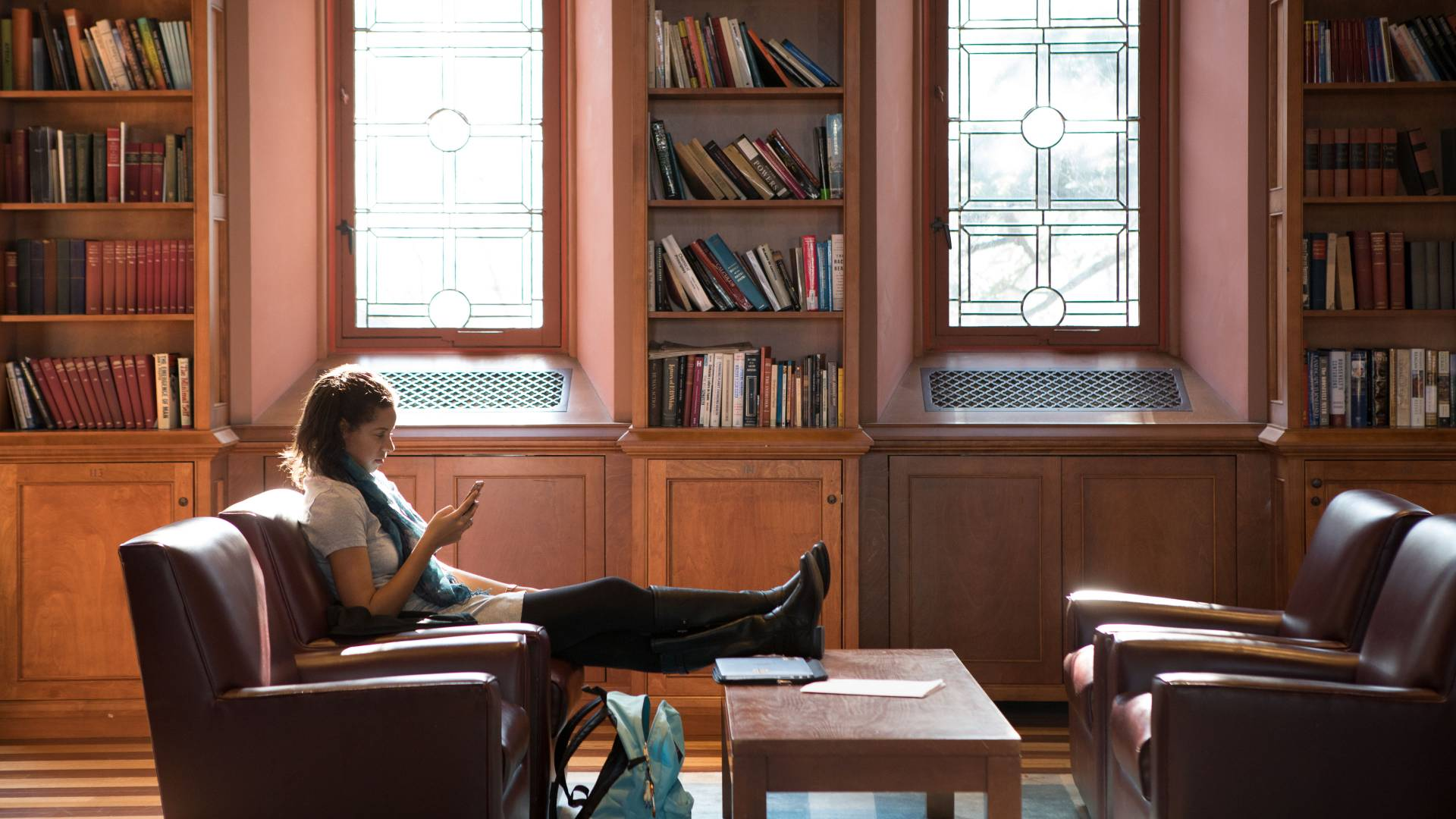Student sitting on chair reading in library