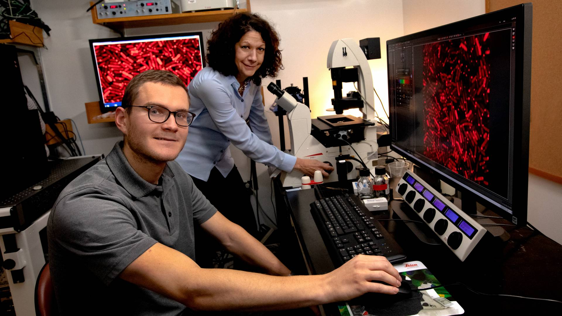 Bonnie Bassler and Justin Silpe sit at a computer station and a microscope, looking at bacteria