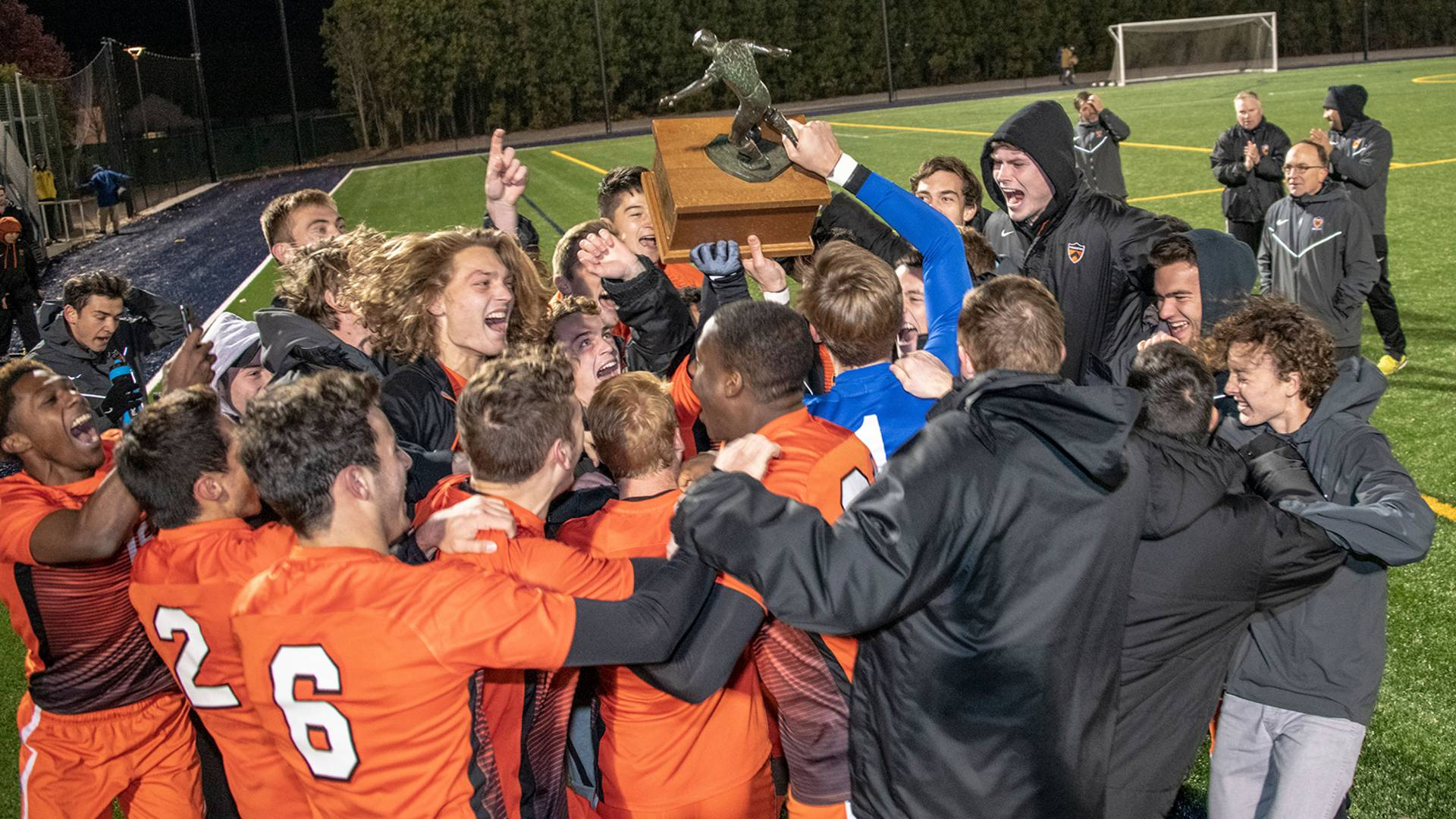 Soccer team celebrates and holds trophy