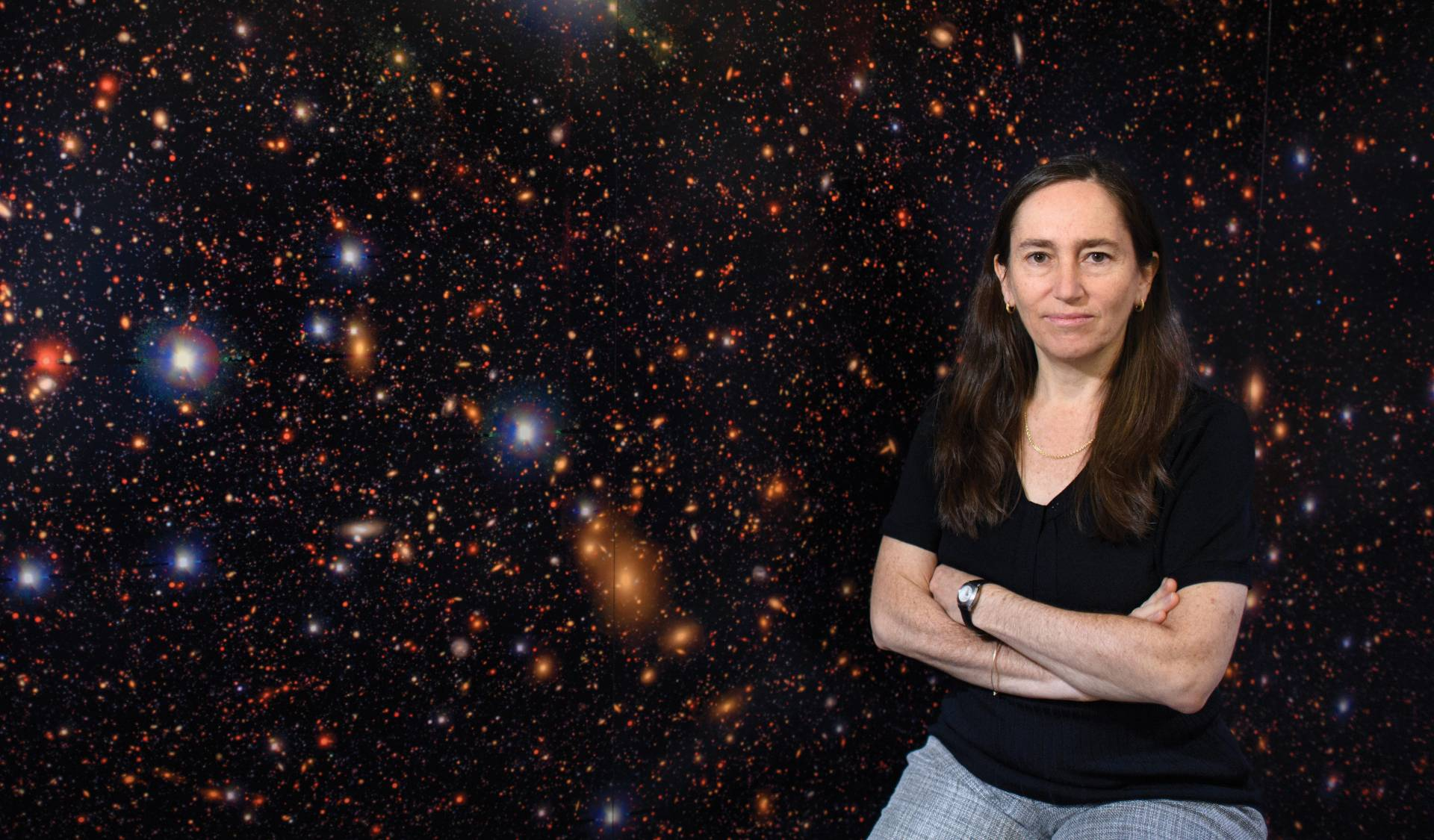 Eve Ostriker sits in front of a satellite photo of stars and planets