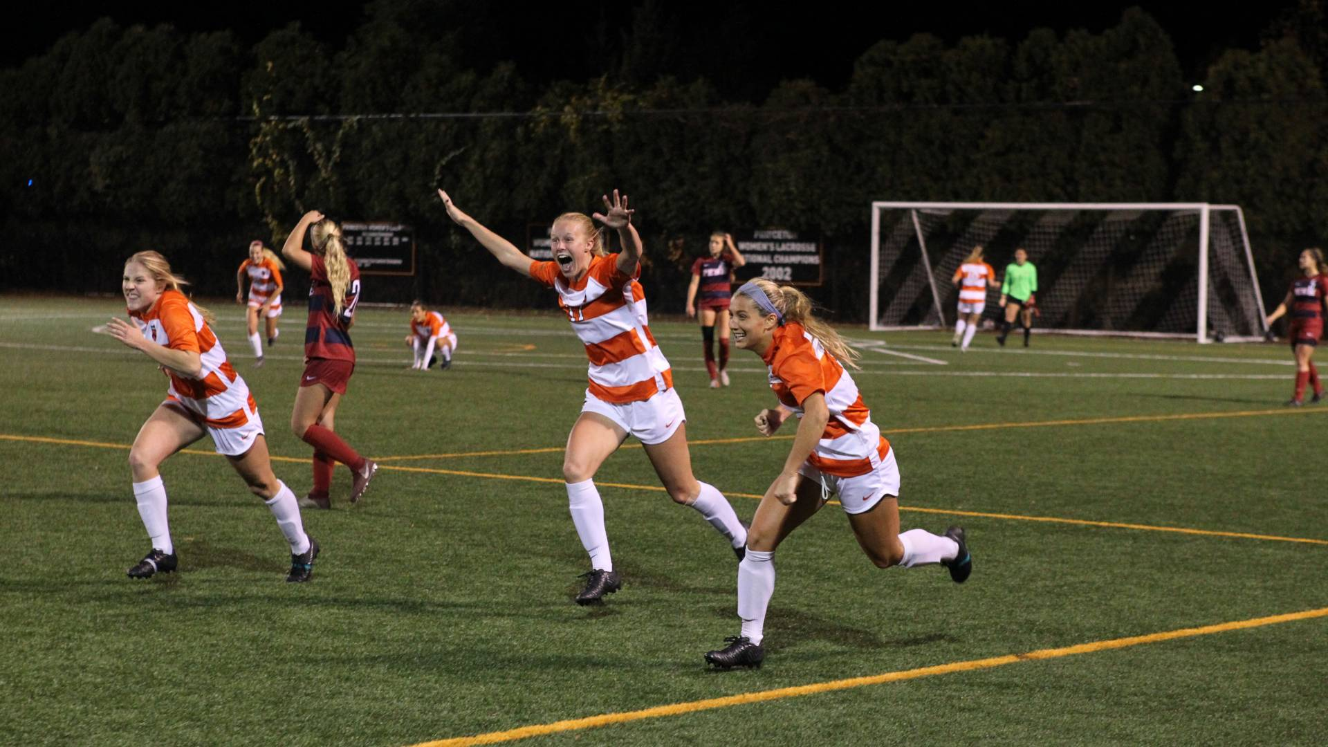 Women's soccer team celebrating on soccer field