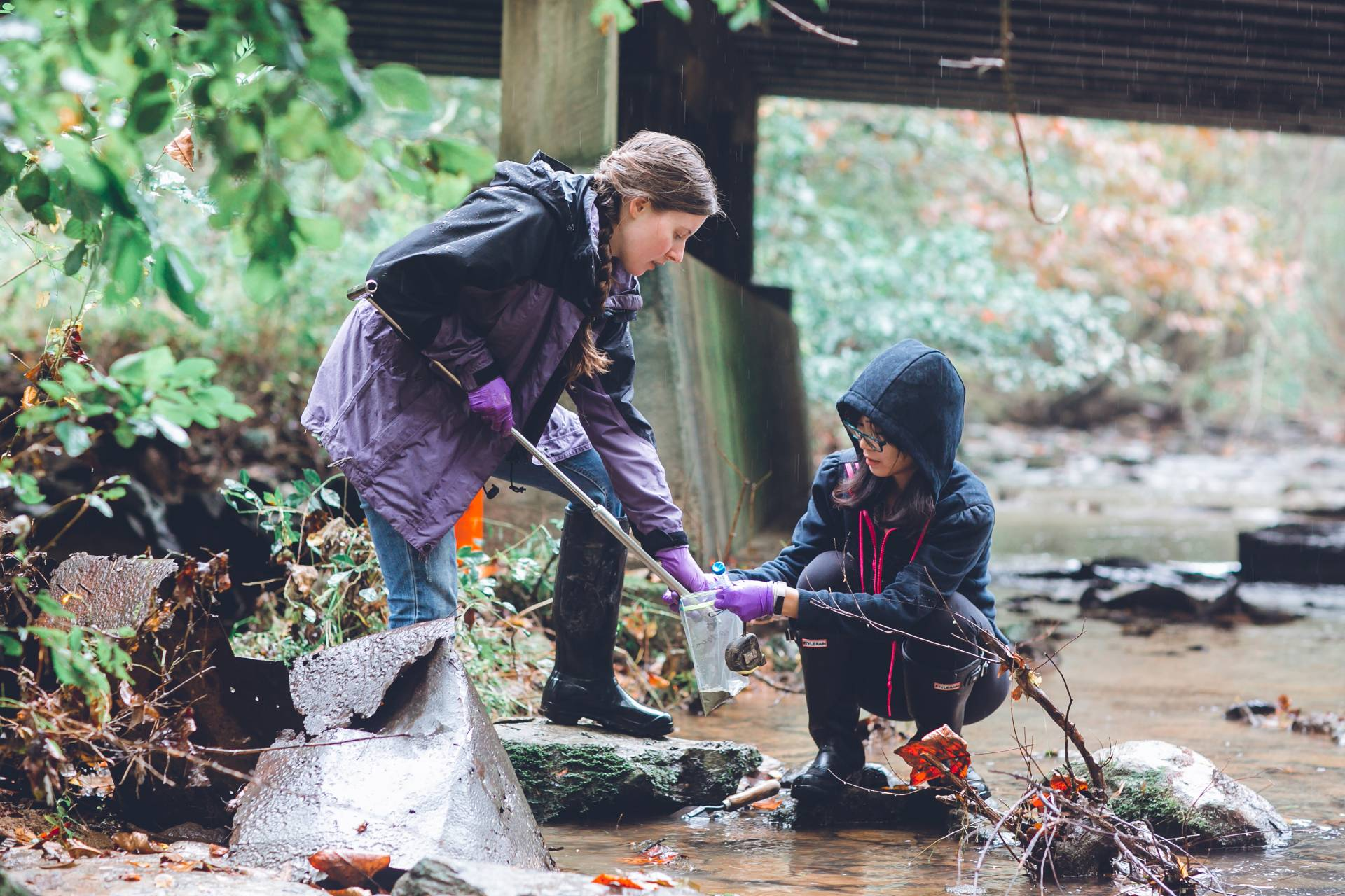 Two students collecting water samples from the bank of a river