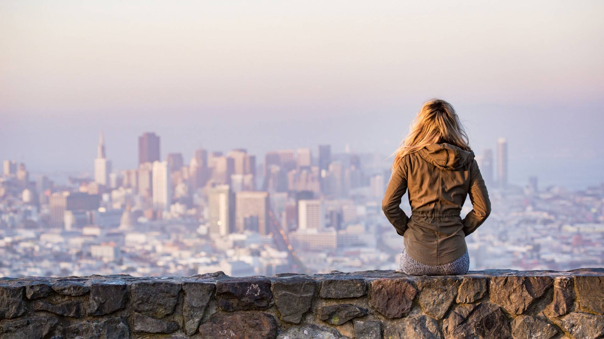 Girl sitting on a stone wall looking out over a city