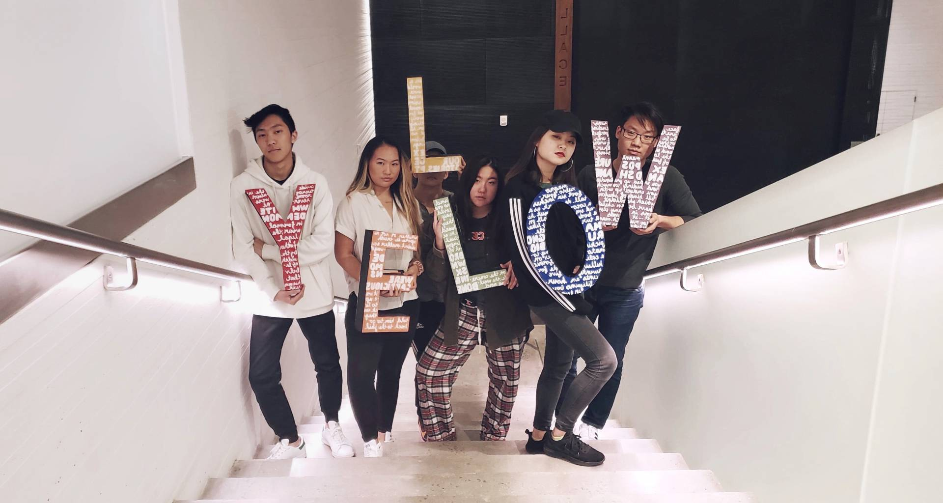 "Six Asian students hold up letters spelling the word, ""YELLOW"""