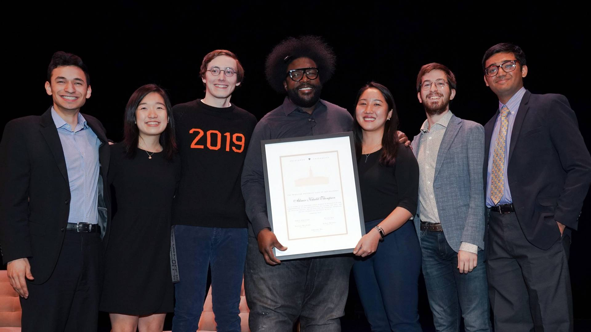 Questlove standing with Princeton seniors holding a certificate for honorary membership of the Class of 2019