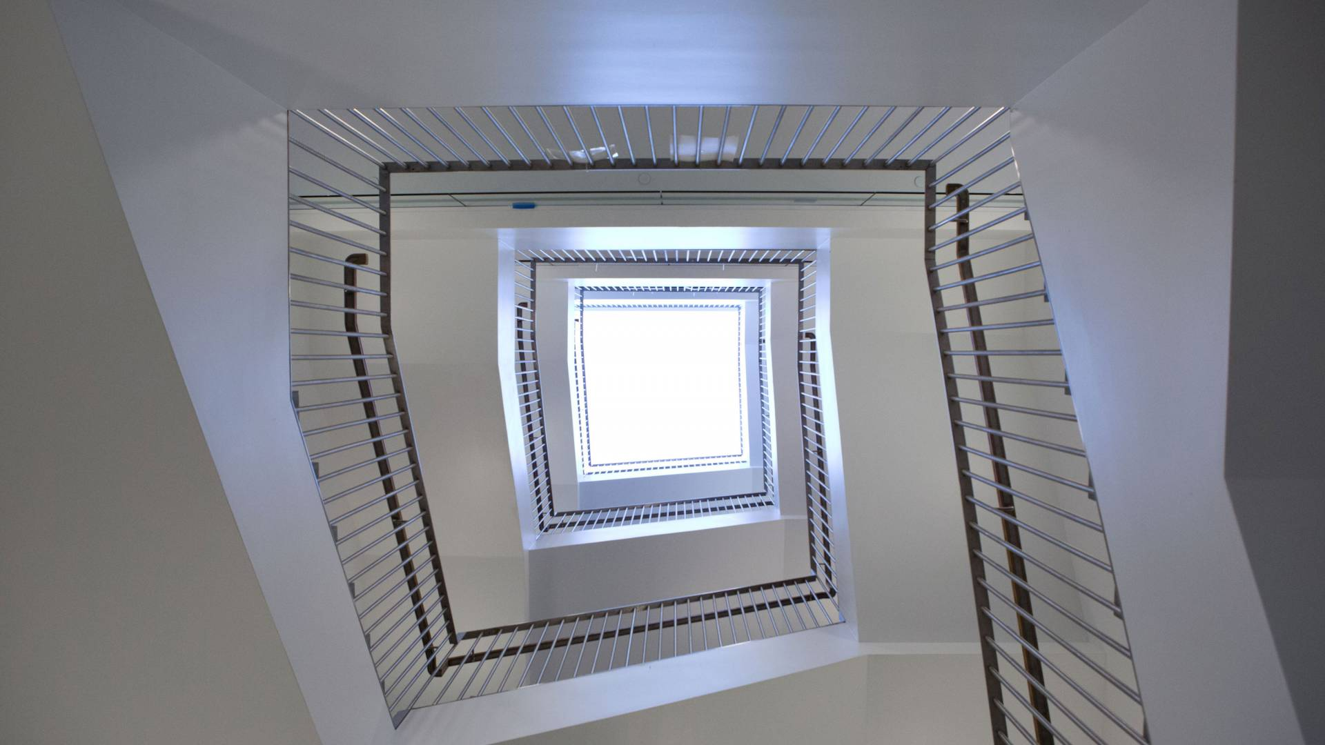 Looking up at a skylight surrounded by a staircase