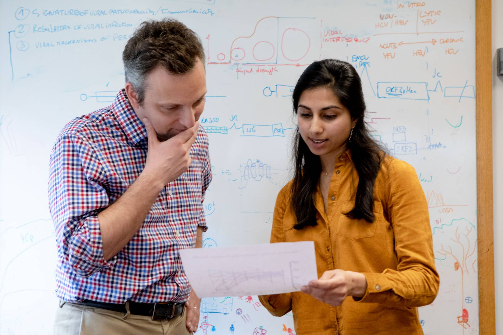 Alexander Ploss and Ila Nimgaonkar looking at paper