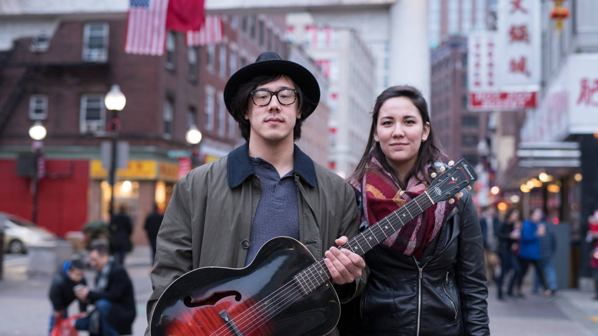 Young man in a hat holding an acoustic guitar standing next to a young woman