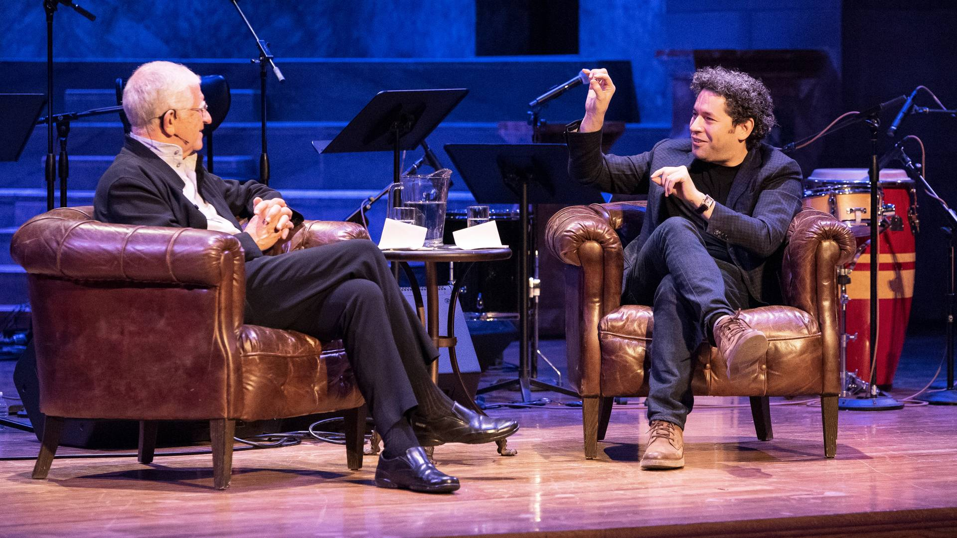 Don Michael Randal sitting on stage with Gustavo Dudamel