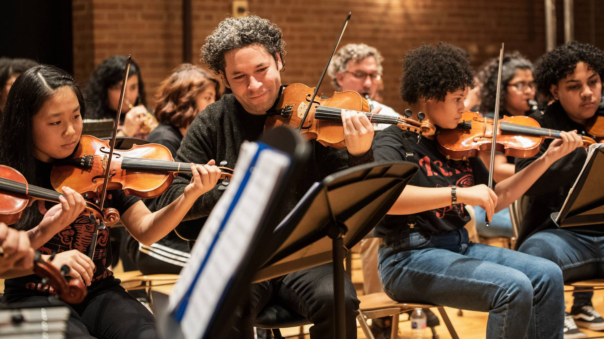 Gustavo Dudamel playing violin with student orchestra