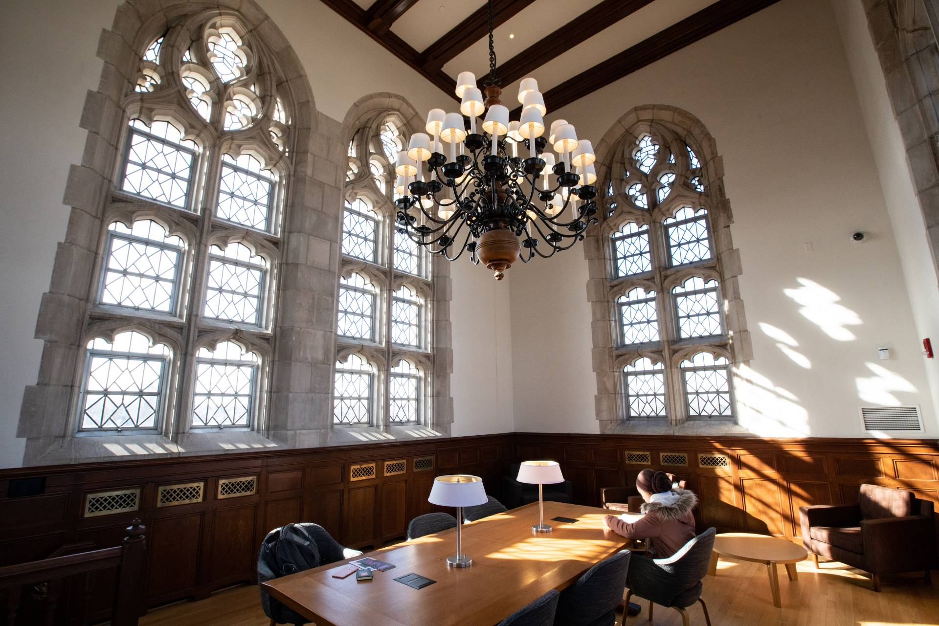 Student studying in room with large high windows and chandeliers