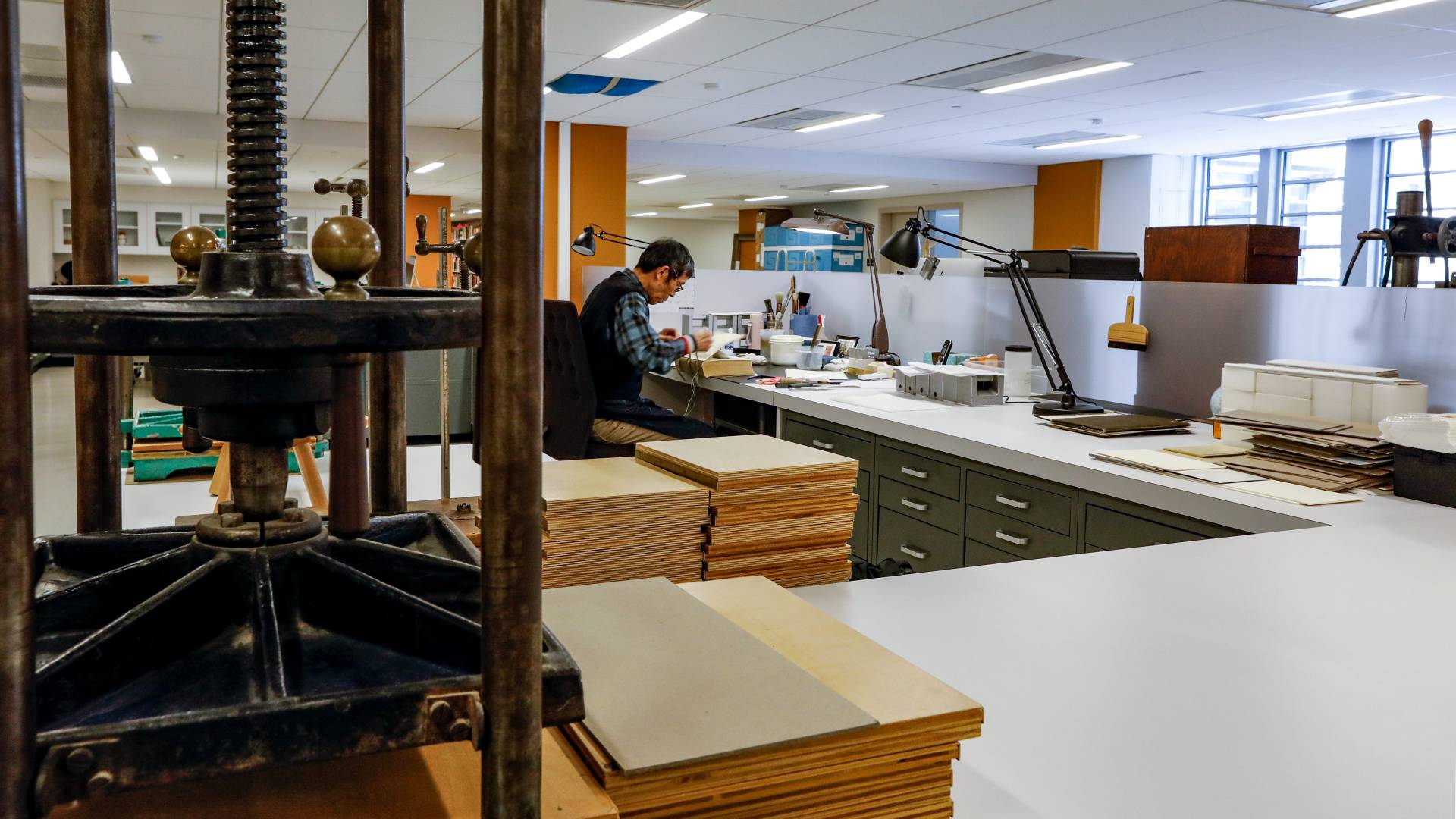 Librarian working at desk in library conservation lab