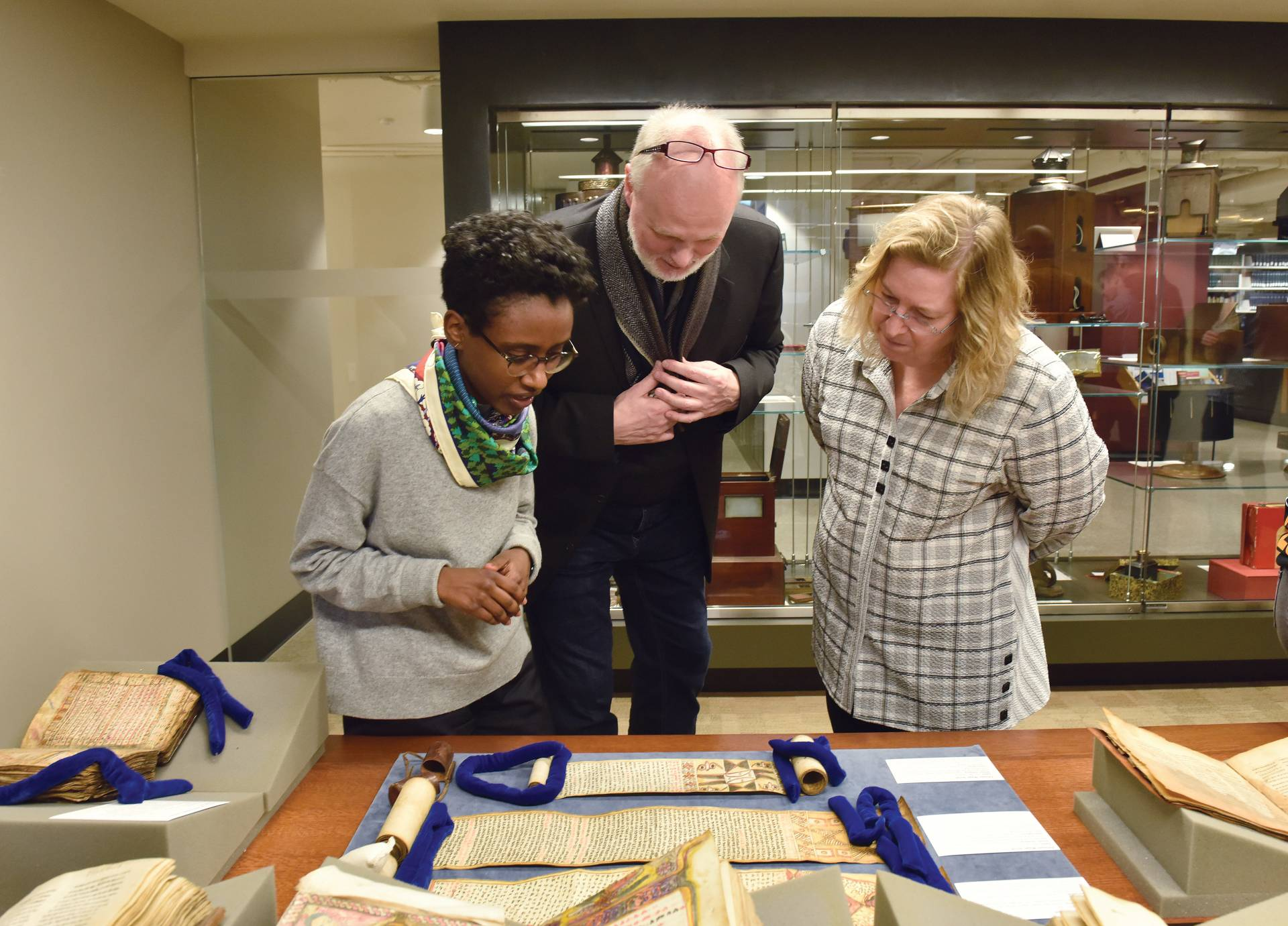Meseret Oldjira, Michael Kleiner, and Wendy Belcher, looking at and discussing a manuscript on a table display.