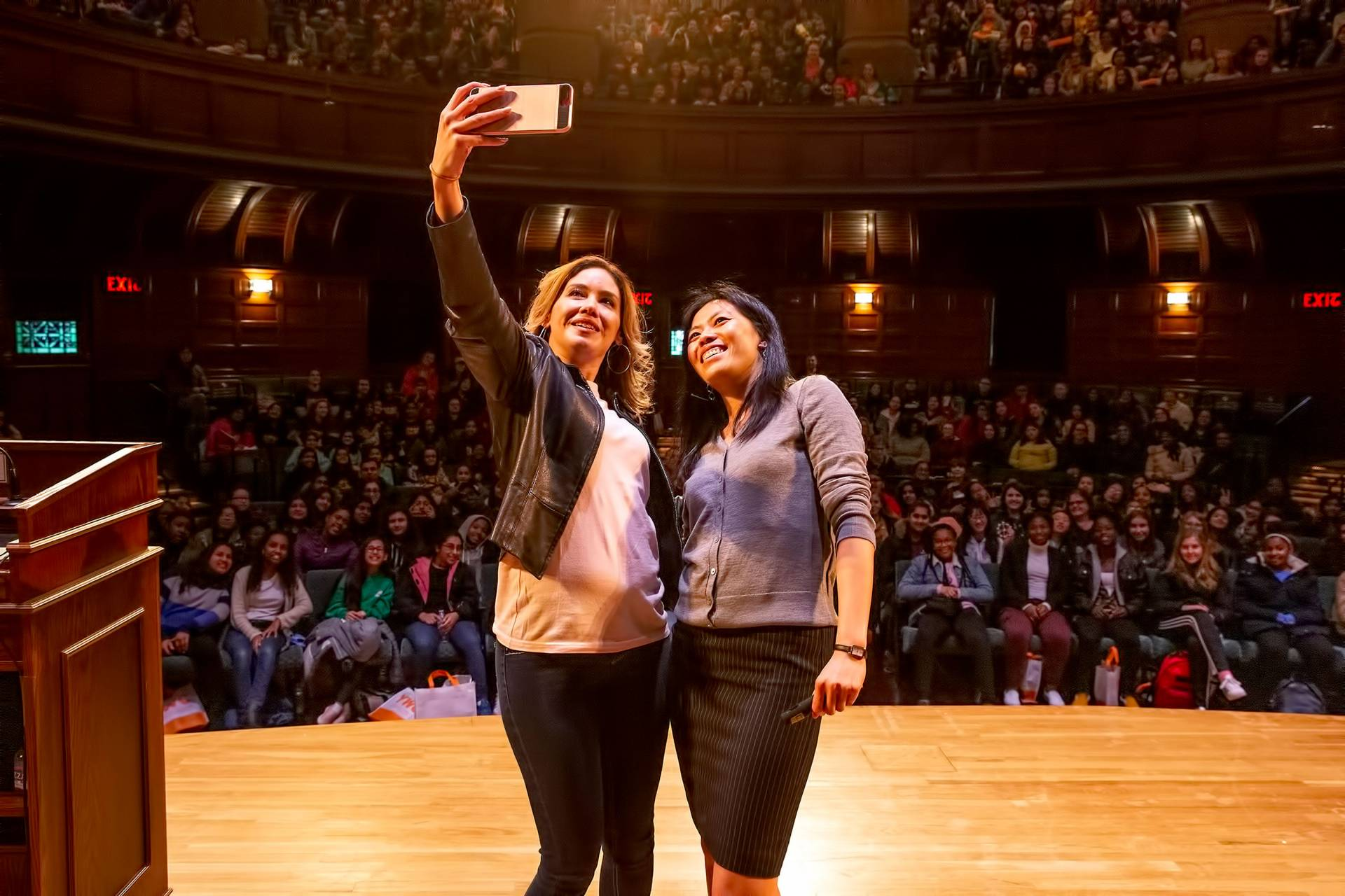 Deedee Ortiz taking a selfie on stage with Tammy Ma