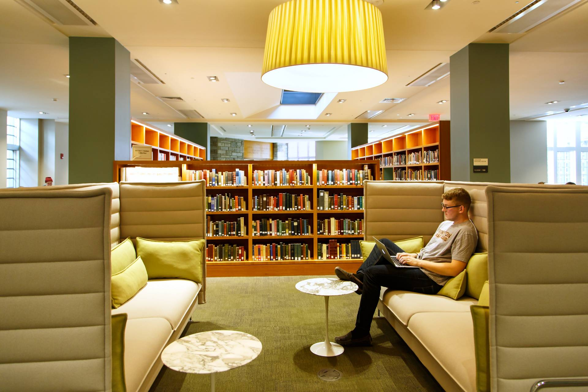 Student sitting on large green couch in library room
